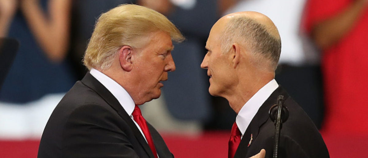ESTERO, FL - OCTOBER 31: President Donald Trump greets Florida Governor and Republican senate candidate Rick Scott as he is introduced during a campaign rally at the Hertz Arena on October 31, 2018 in Estero, Florida. President Trump continues travelling across America to help get the vote out for Republican candidates running for office. (Photo by Joe Raedle/Getty Images)