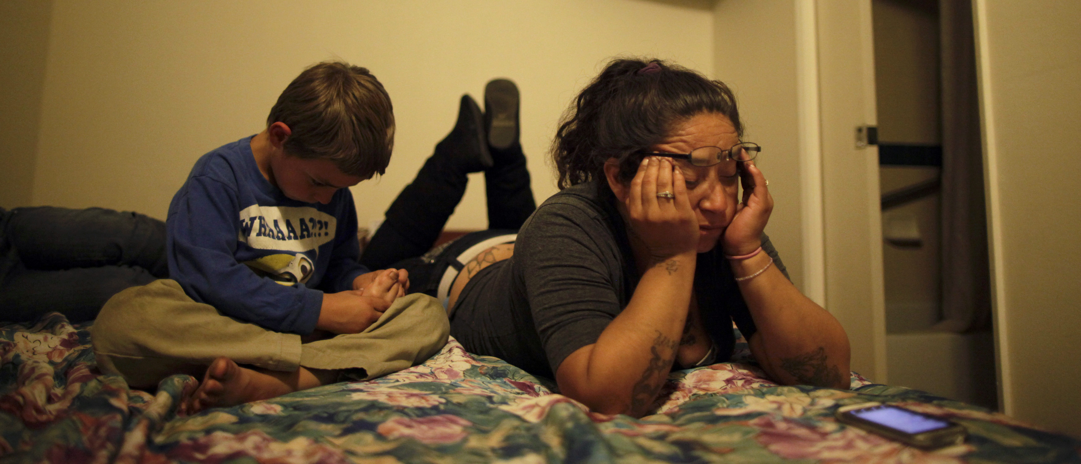 Angelica Cervantes, 36, (R) and her son Tomas Cervantes, 6, sit in a motel room, in Port Hueneme, some 65 miles northwest of Los Angeles, California February 28, 2012. REUTERS/Lucy Nicholson (UNITED STATES - Tags: SOCIETY) - GM1E83A05B901