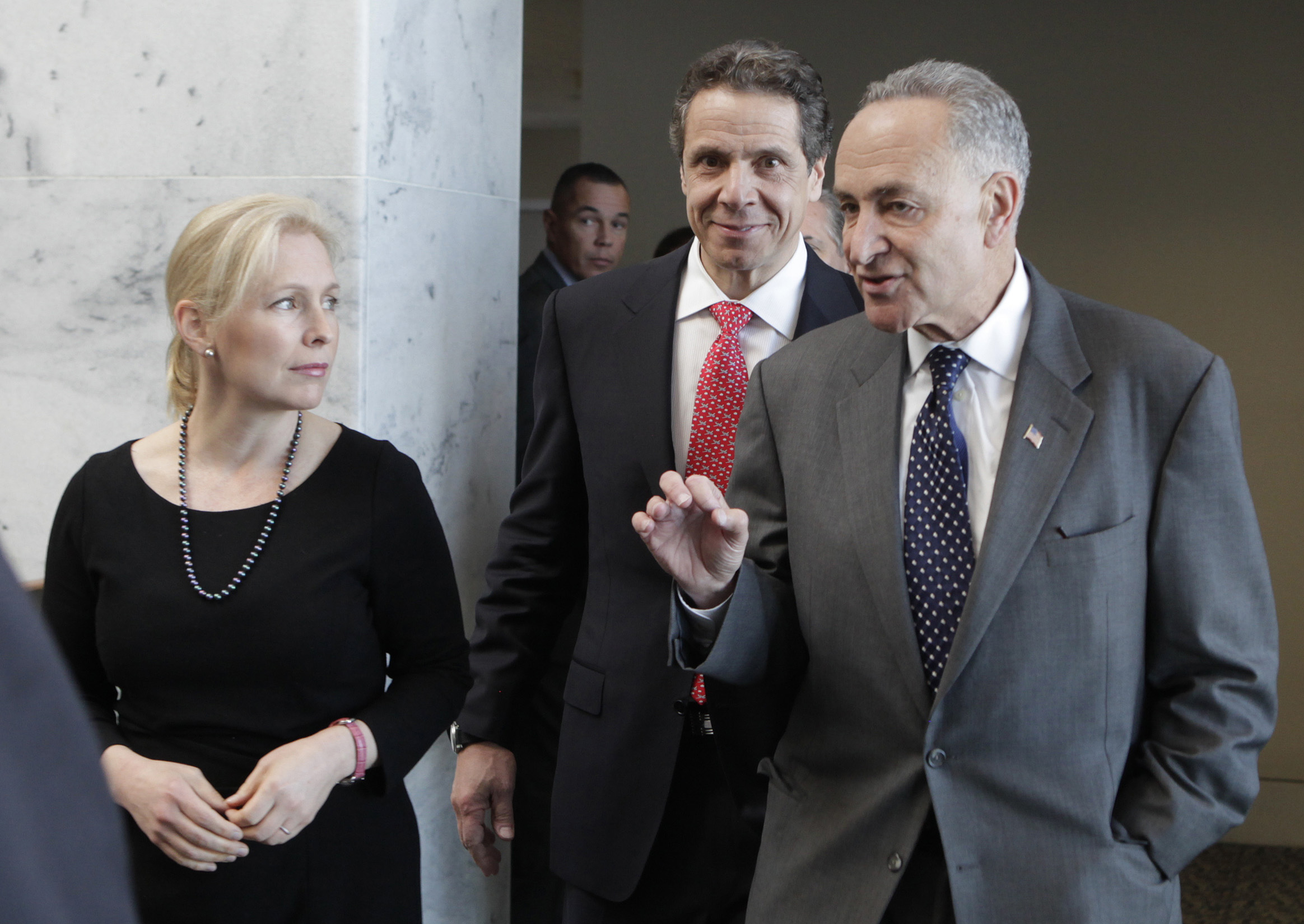New York Governor Cuomo walks with Senators Schumer and Gillibrand in Washington
