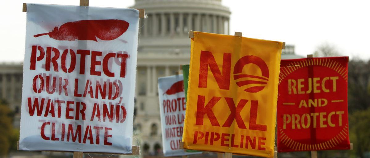 Members of the Cowboys and Indian Alliance, a group of ranchers, farmers and indigenous leaders, lift their signs in protest against the Keystone XL pipeline in front of the U.S. Capitol in Washington on April 22, 2014. REUTERS/Gary Cameron