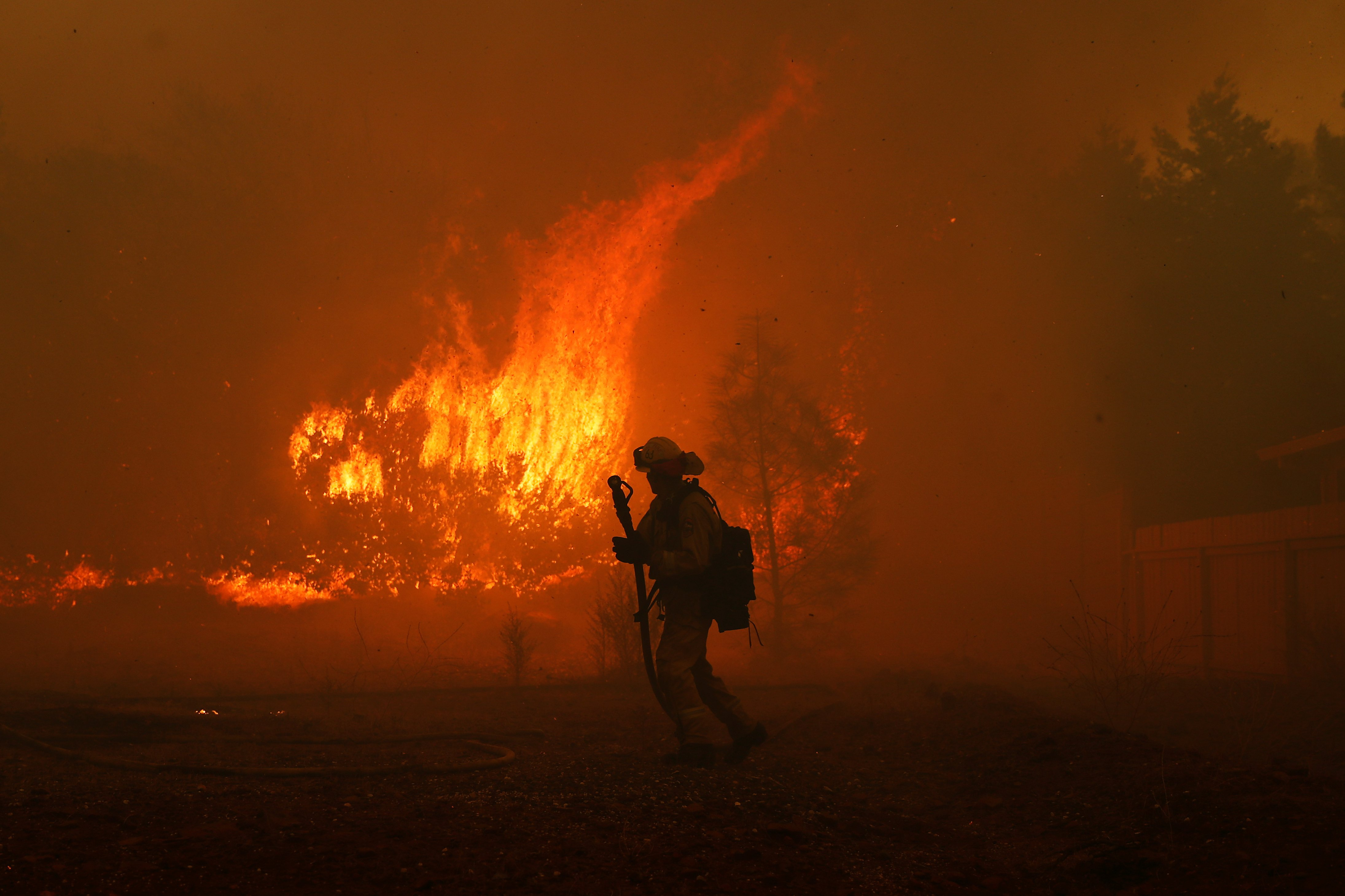 A Cal Fire firefighter monitors a fire near a home while battling the Camp Fire in Paradise