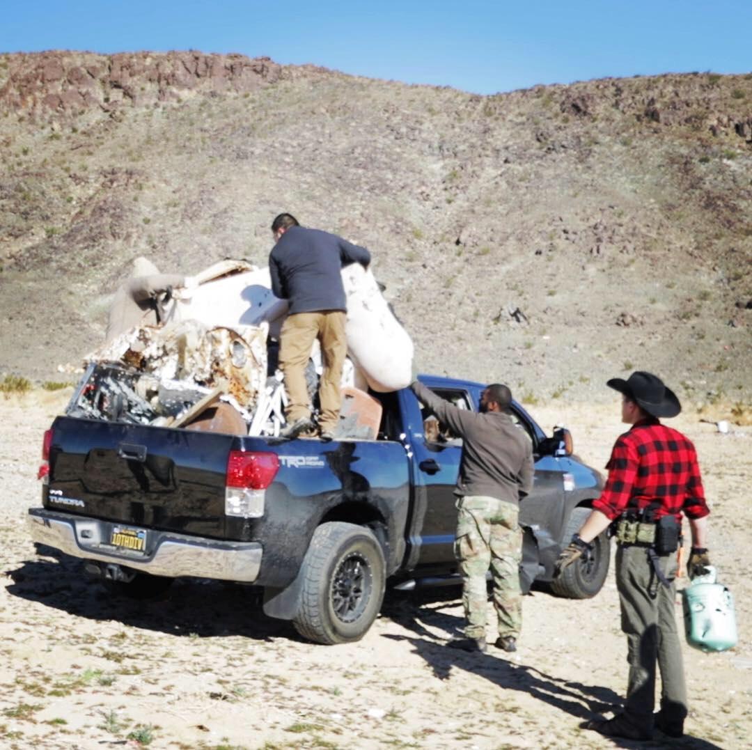 Staff load trash onto a truck near Joshua Tree National Park in California