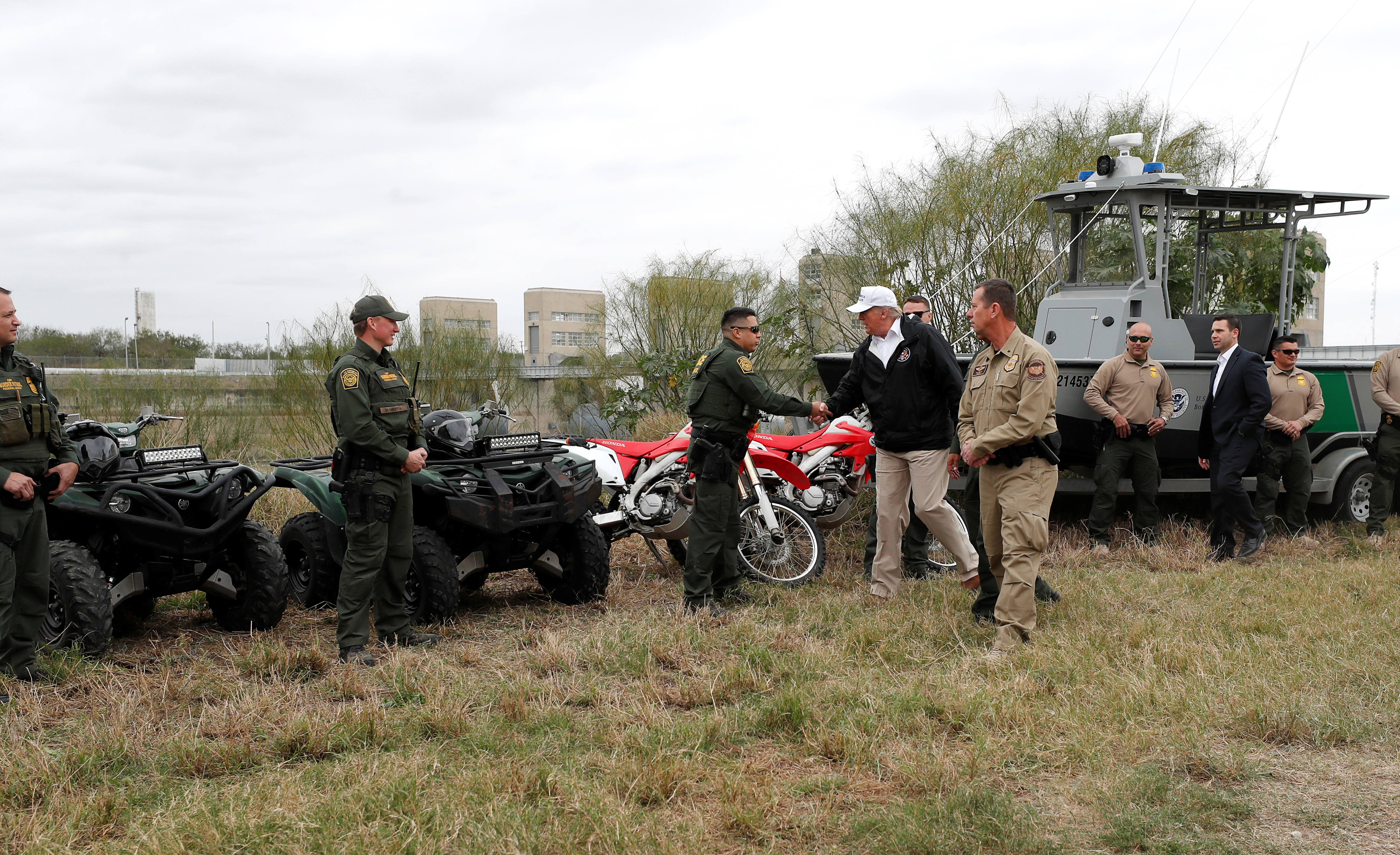 U.S. President Donald Trump greets U.S. Border Patrol agents standing with their all terrain vehicles, motorcycles and a boat on the banks of the Rio Grande River during his visit to the U.S. - Mexico border in Mission, Texas, U.S., January 10, 2019. REUTERS/Leah Millis