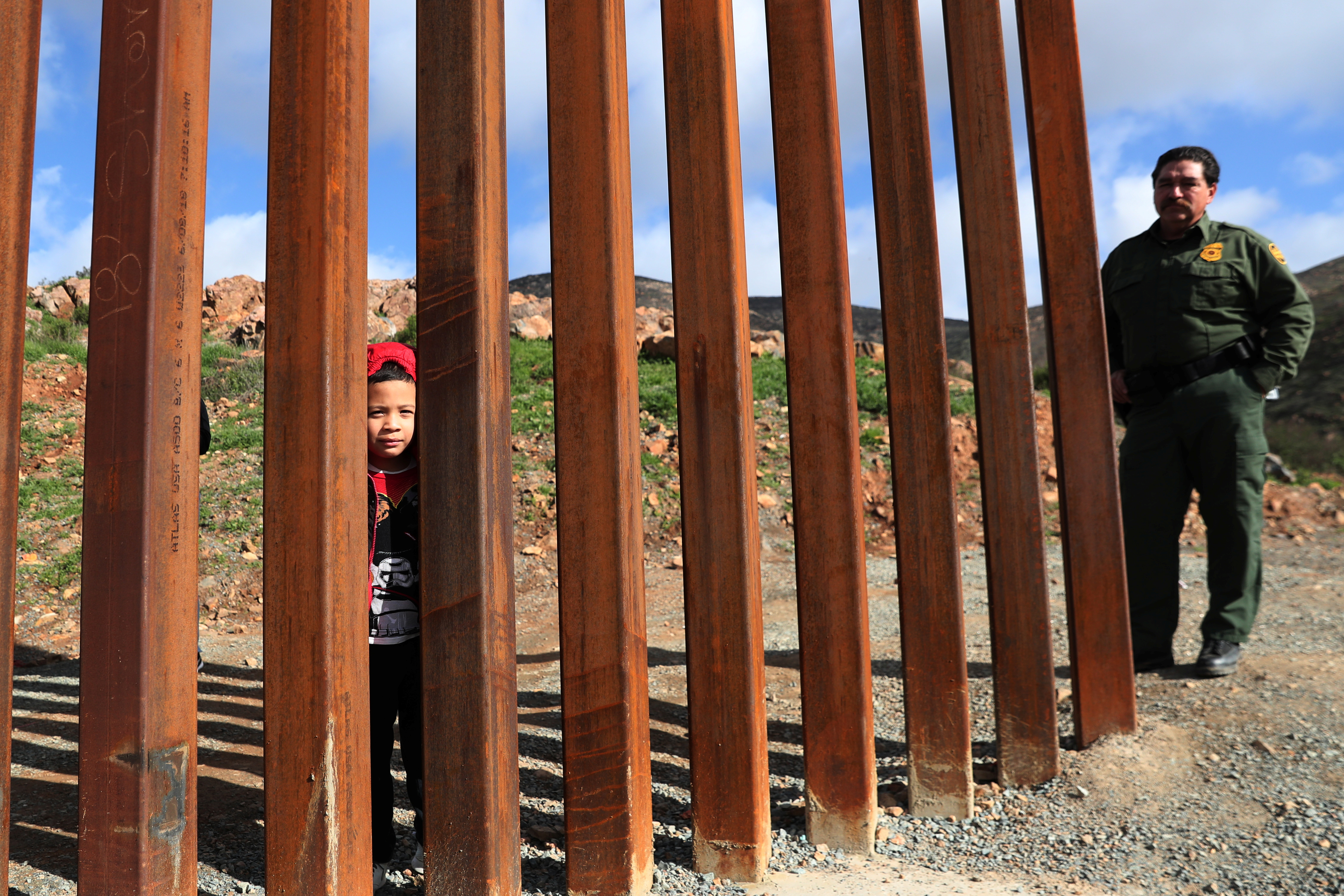 A boy from Honduras looks through the U.S. and Mexico border fence after being detained by U.S. Border Patrol in Tijuana, Mexico, January 21, 2019. REUTERS/Shannon Stapleton