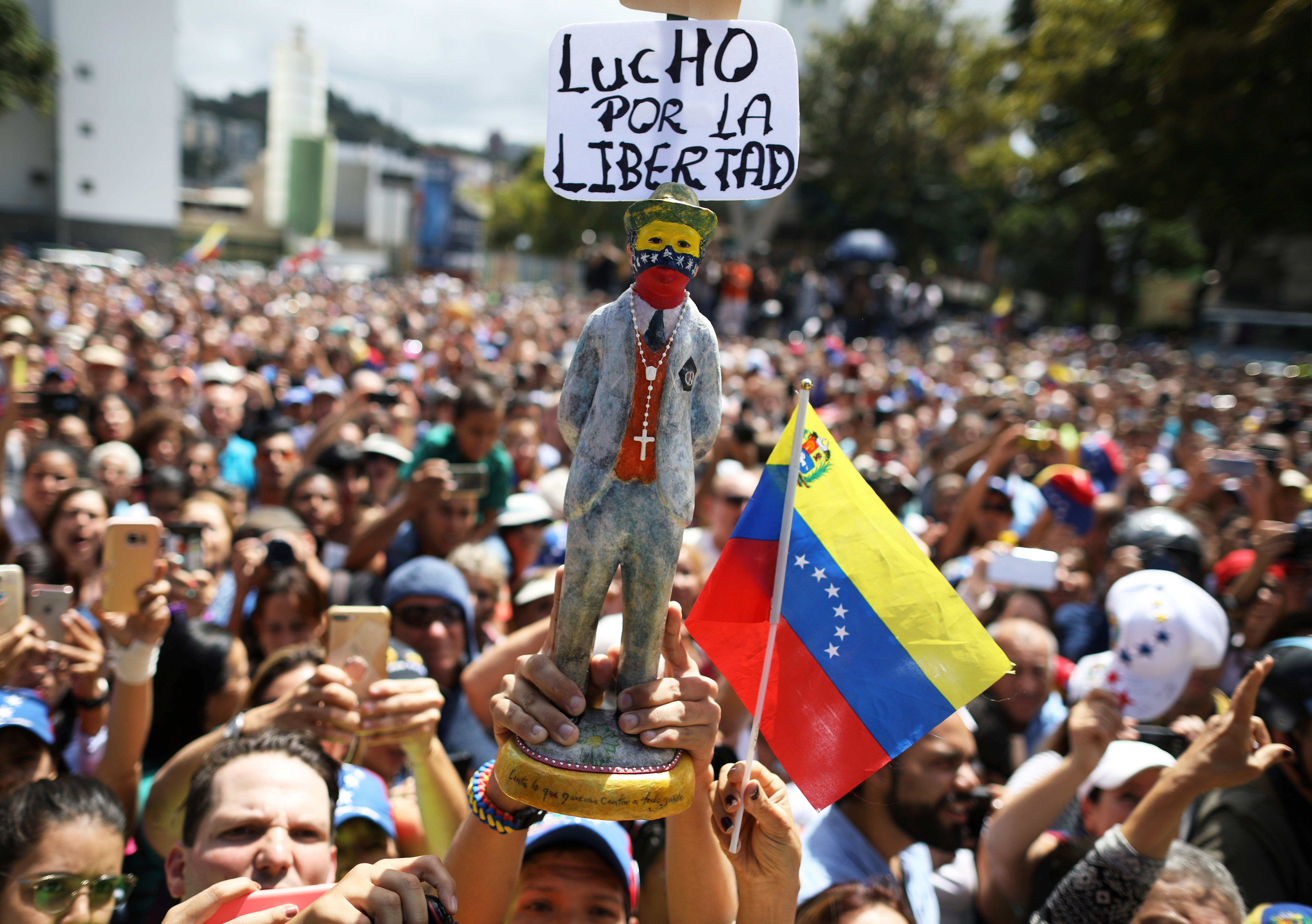 "Supporters of Venezuela's opposition leader Juan Guaido hold a figurine with a sign that reads: ""I fight for freedom"", during a rally with members of the Venezuela's National Assembly regarding an amnesty law project for members of the military, in Caracas, Venezuela, January 26, 2019. REUTERS/Andres Martinez Casares"