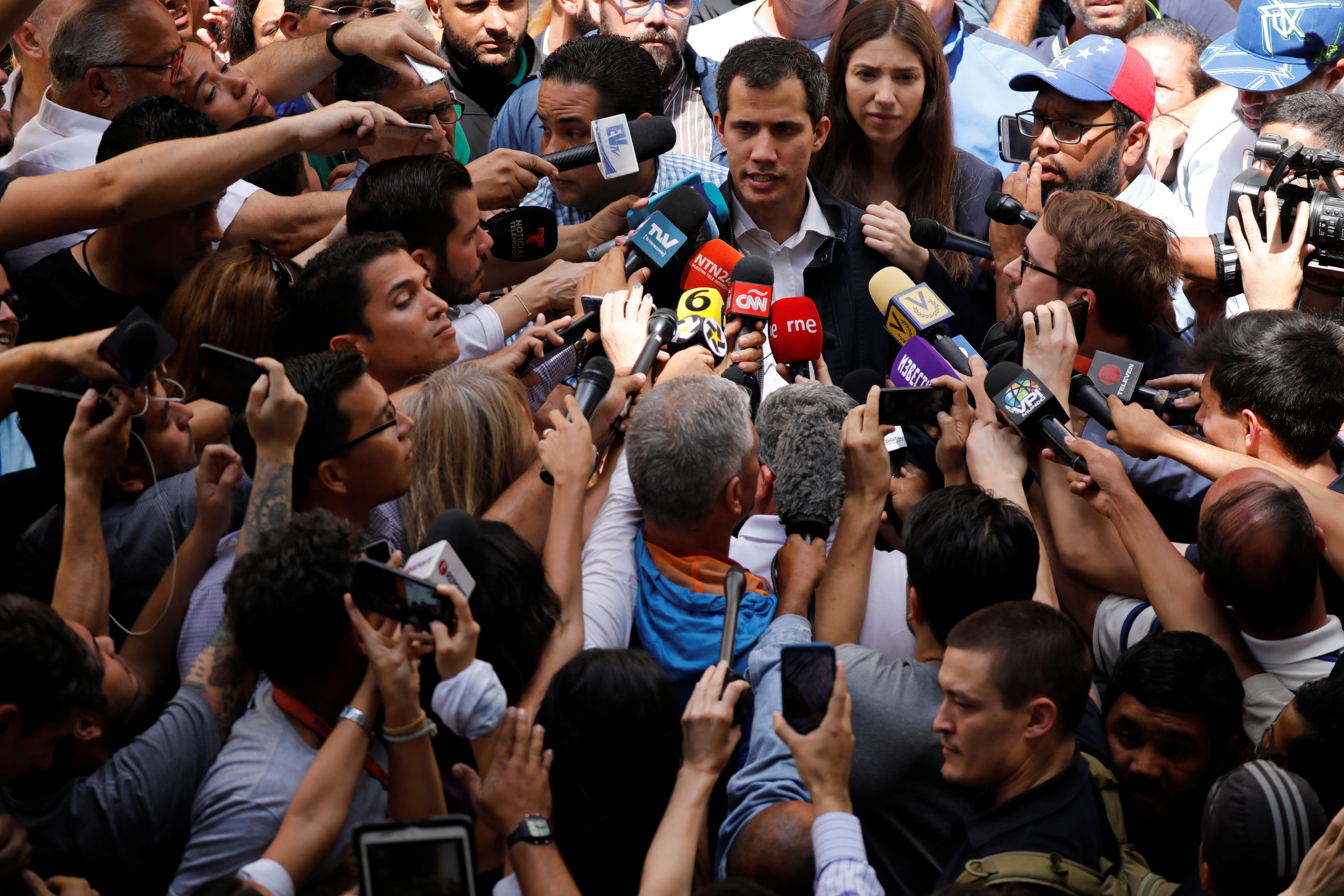 Venezuelan opposition leader and self-proclaimed interim president Juan Guaido accompanied by his wife Fabiana Rosales, speaks to the media after a holy Mass at a local church in Caracas, Venezuela, January 27, 2019. REUTERS/Carlos Barria