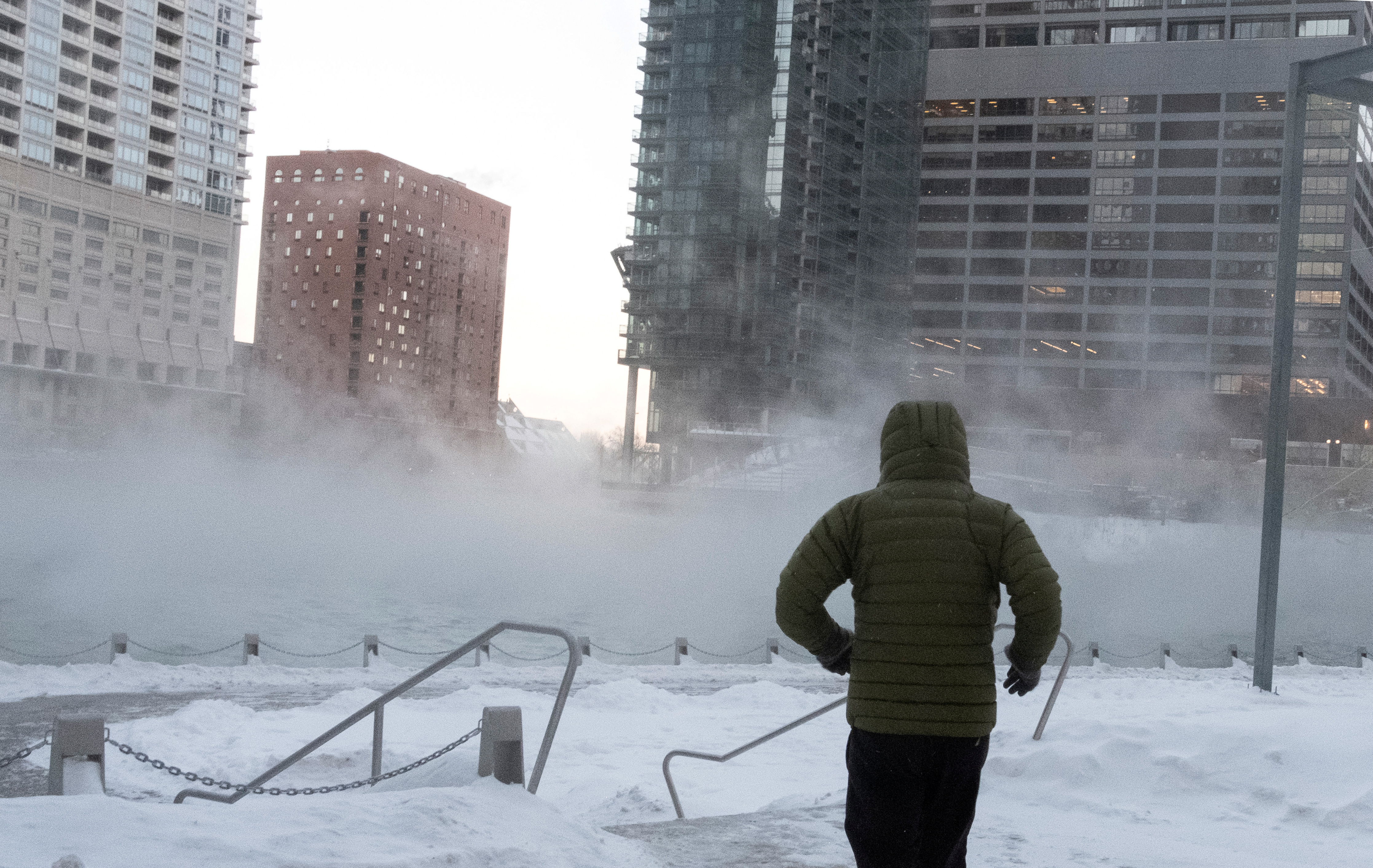 A man runs by the Chicago River during subzero temperatures carried by the polar vortex, in Chicago