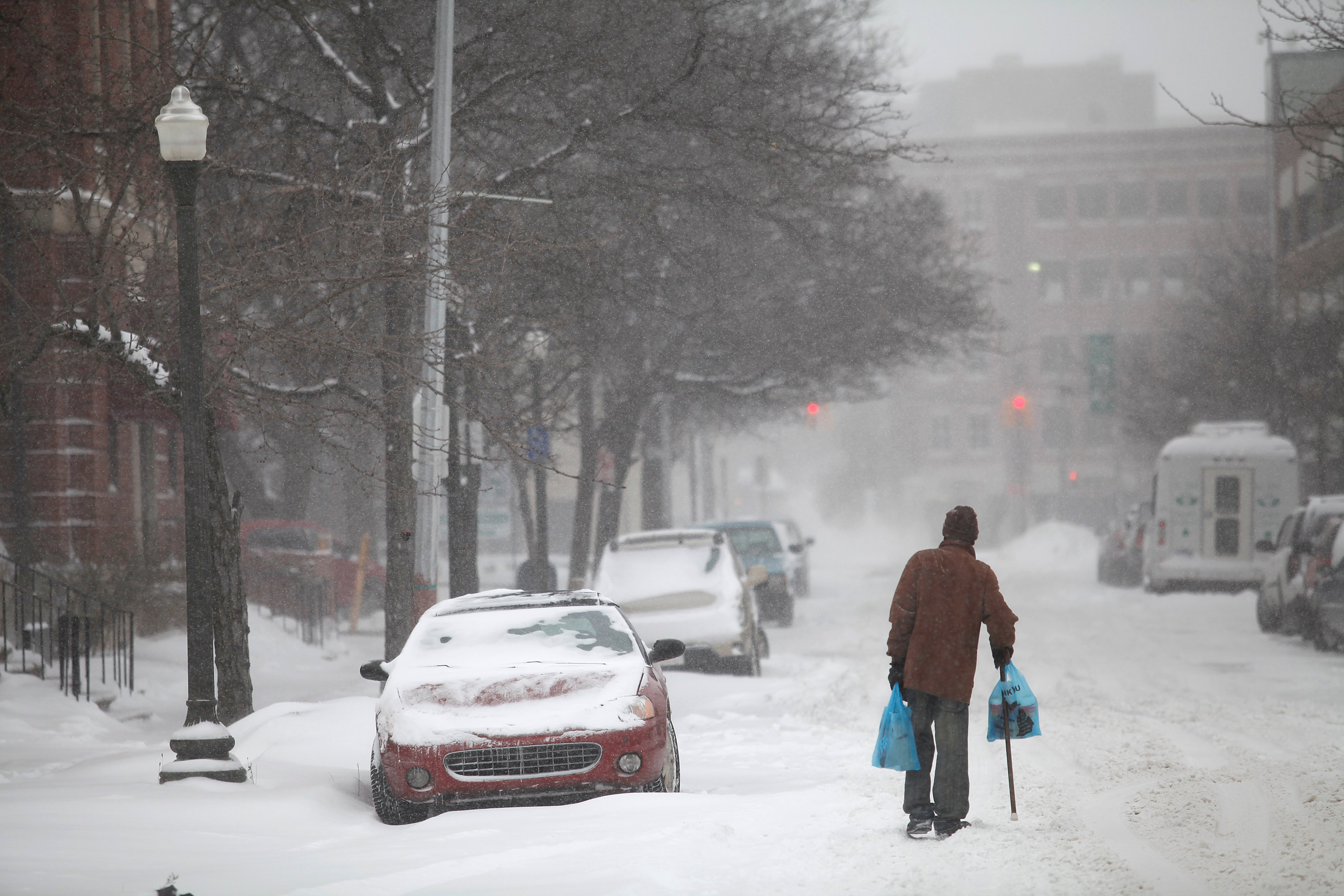 A man uses his cane to navigate a snow covered road in Detroit
