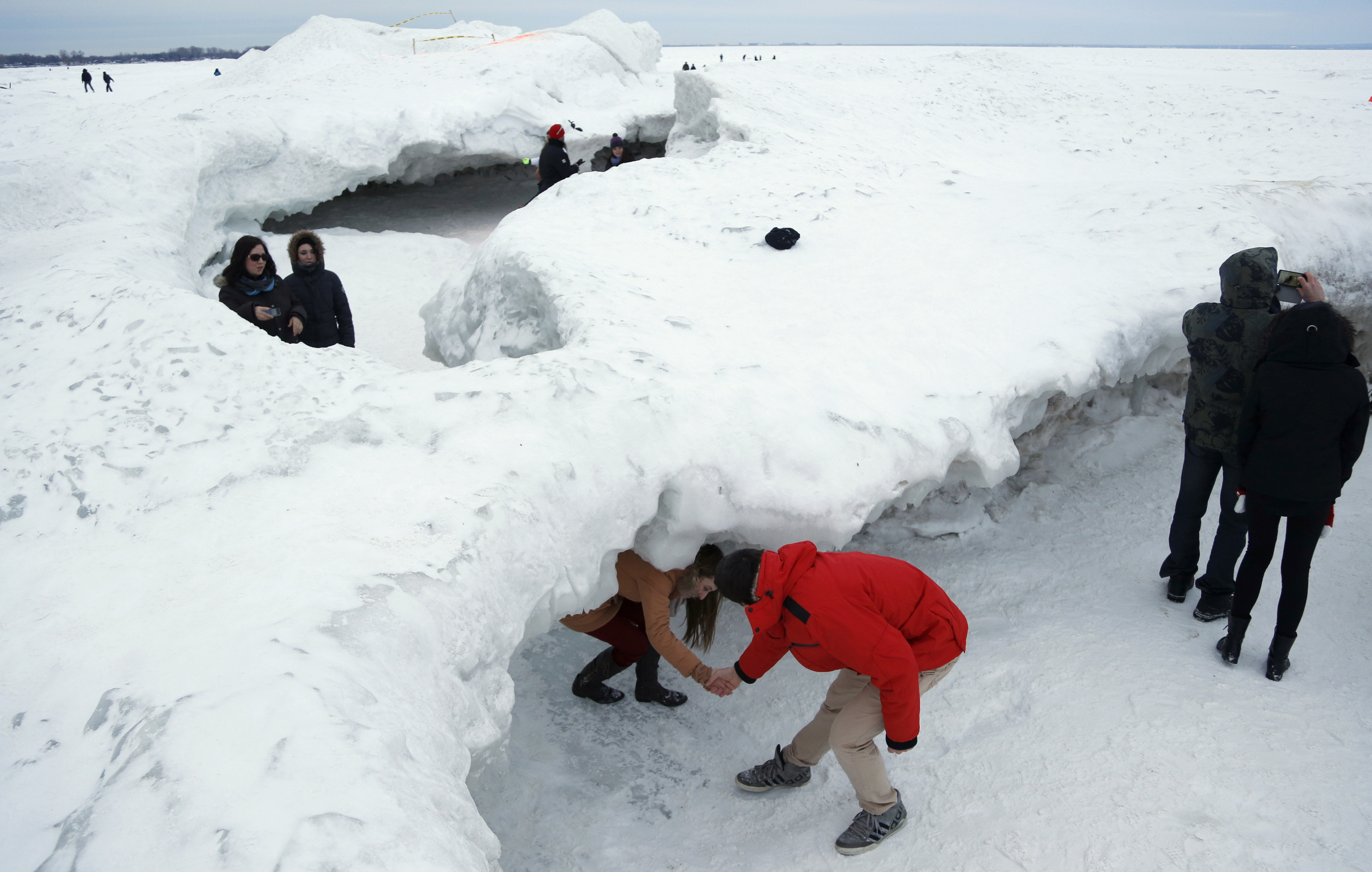 Sightseers make their way under an arch formed by shove ice piling up on the shores of Lake Erie, in Crystal Beach, Ontario