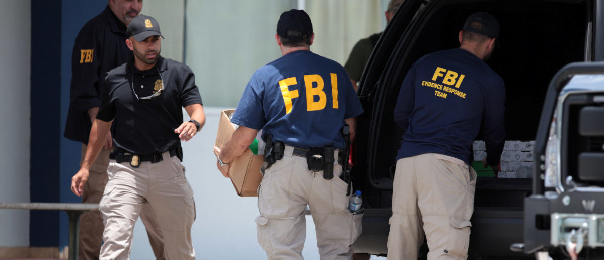 Federal Bureau of Investigation (FBI) personnel load boxes into a car during a raid, in July 19, 2017. REUTERS/Alvin Baez