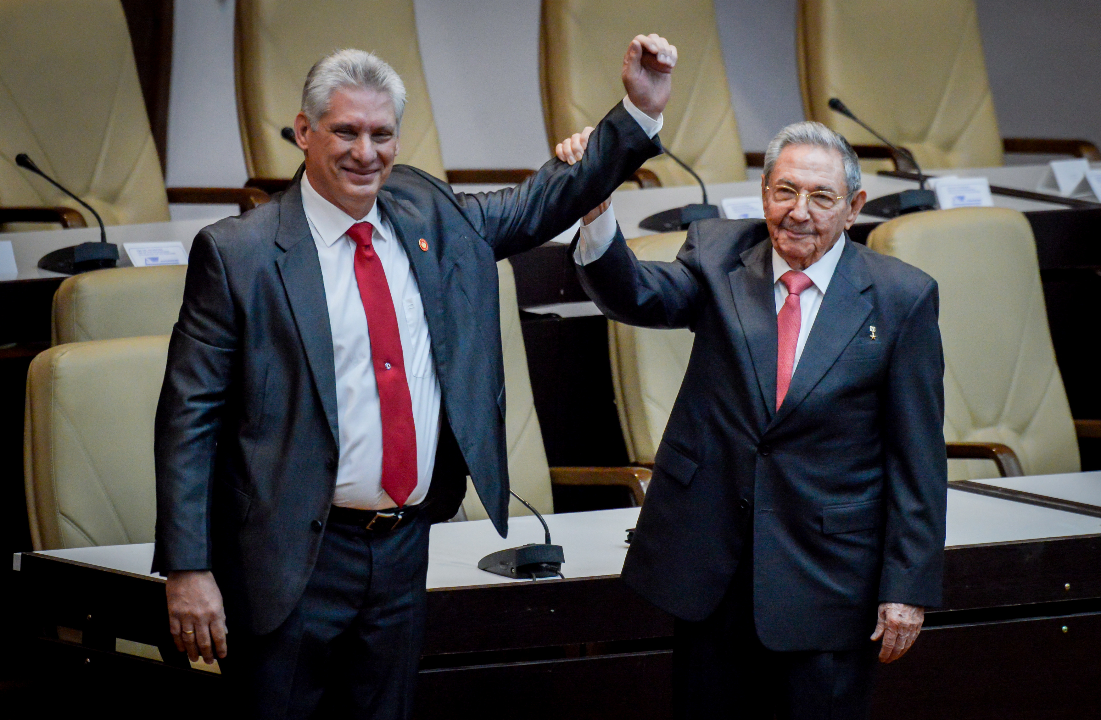 Newly elected Cuban President Miguel Diaz-Canel (L) reacts as former Cuban President Raul Castro raises his hand during the National Assembly in Havana, Cuba, April 19, 2018. REUTERS/Adalberto Roque/Pool via Reuters