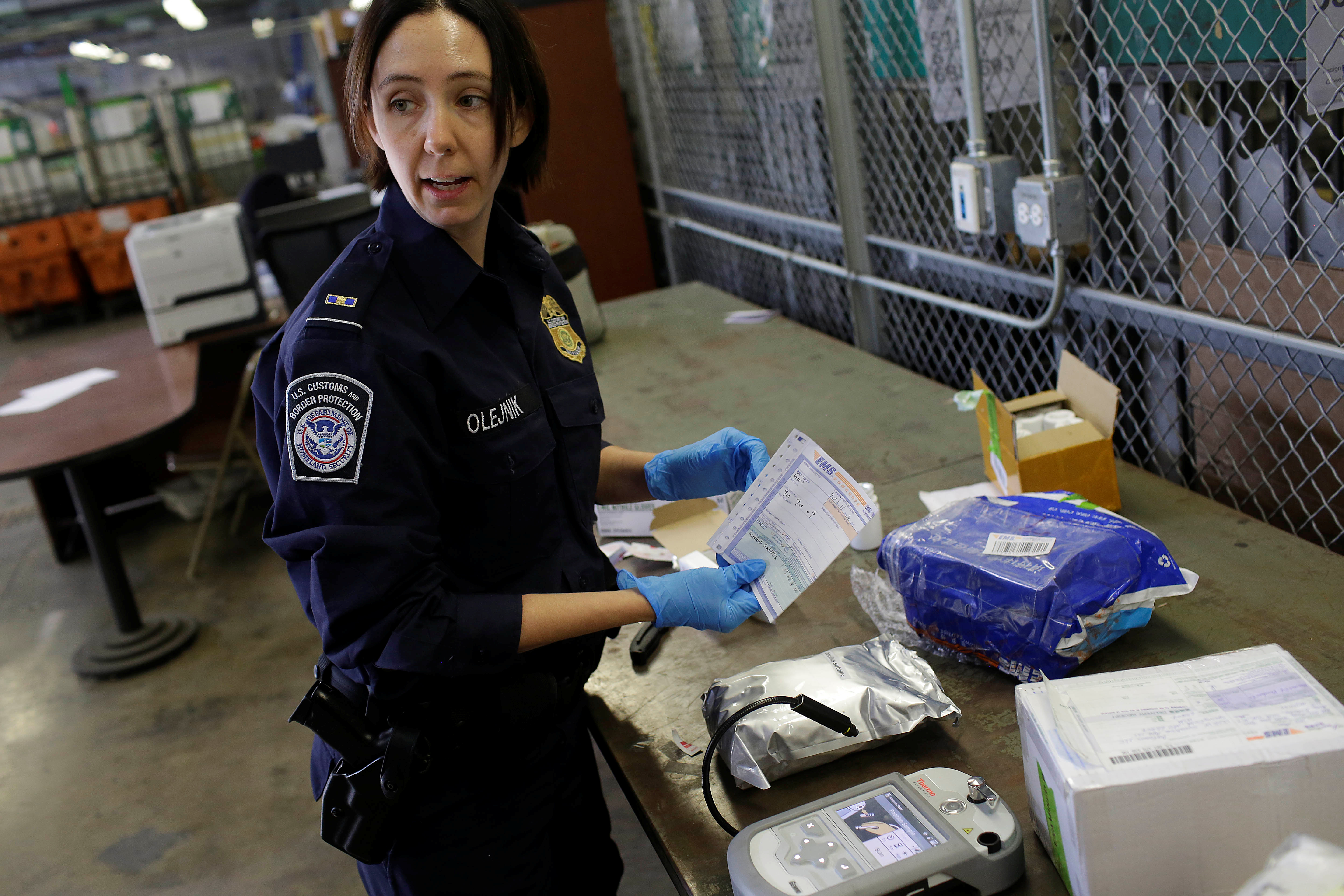 U.S. Customs and Border Protection officer Ella Olejnik looks at the paperwork on a package before inspecting the substance inside at the International Mail Facility at O'Hare International Airport in Chicago, Illinois, U.S. November 29, 2017. Picture taken November 29, 2017. REUTERS/Joshua Lott