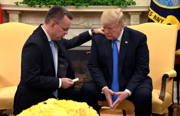 U.S. President Donald Trump closes his eyes in prayer along with Pastor Andrew Brunson, after his release from two years of Turkish detention, in the Oval Office of the White House, Washington, U.S., October 13, 2018. REUTERS/Mike Theiler