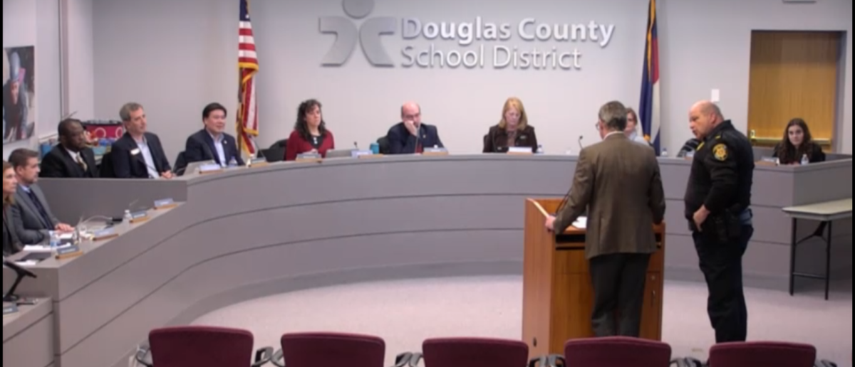 A man was escorted by a police after naming a teacher who allegedly doxxed the wrong Covington Catholic boy. Screenshot/Vimeo/Douglas County School District