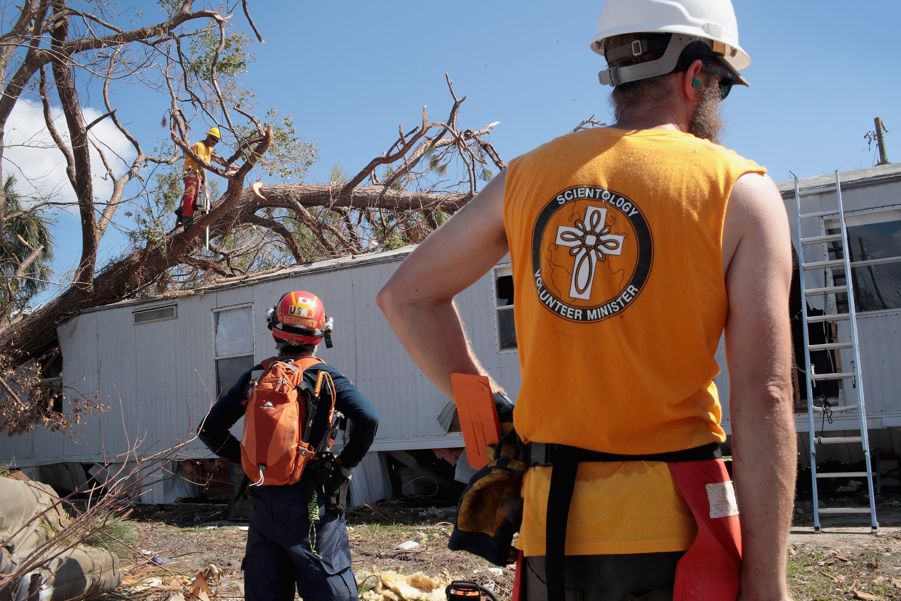 PANAMA CITY, FL - OCTOBER 20: Volunteers from the Scientology Volunteer Ministers help to clear debris left by Hurricane Michael at the severely-damaged Bay Oaks Village trailer park on October 20, 2018 in Panama City, Florida. (Photo by Scott Olson/Getty Images)