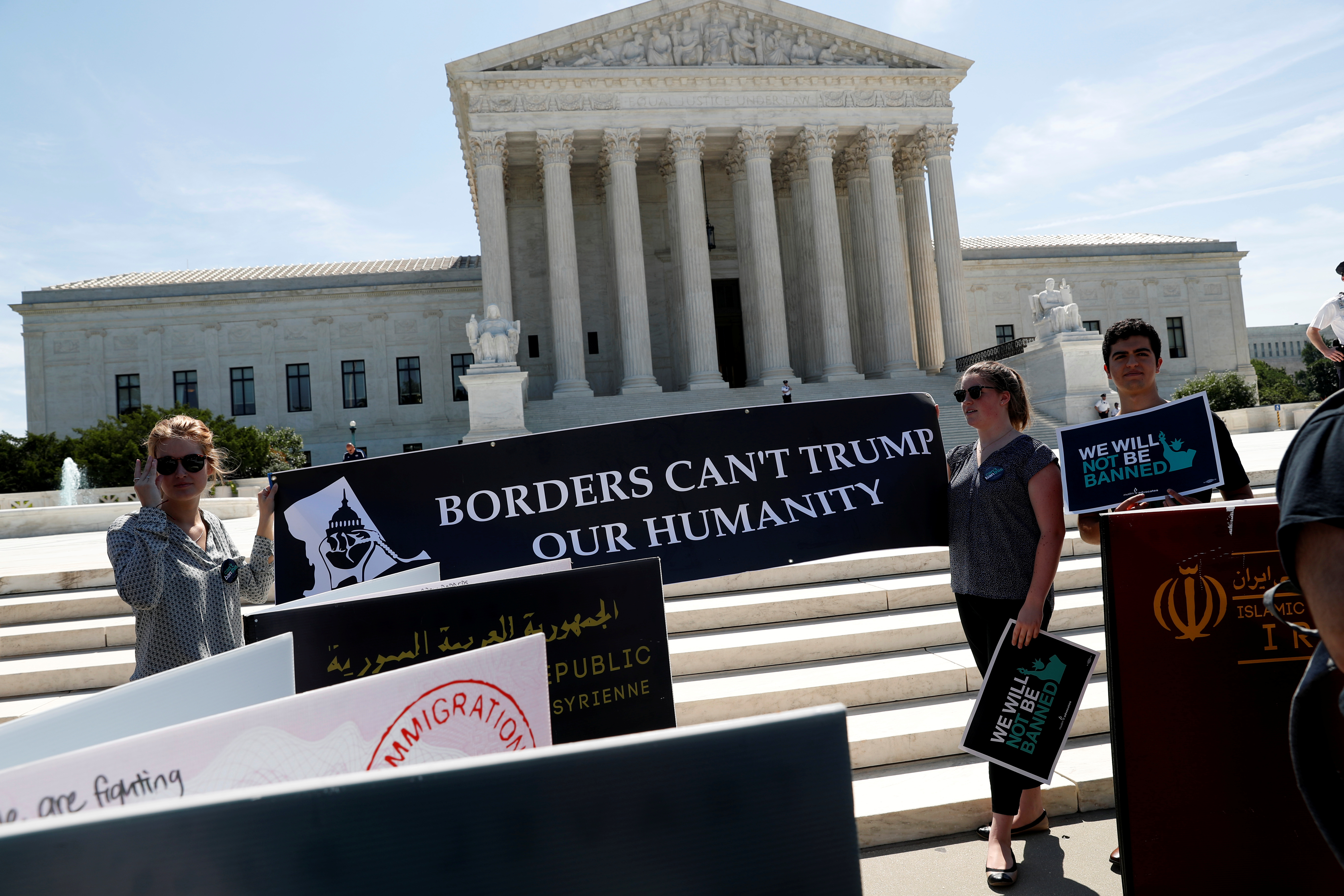 Immigration rights proponents demonstrate outside the Supreme Court in Washington. June 26, 2018. REUTERS/Leah Millis