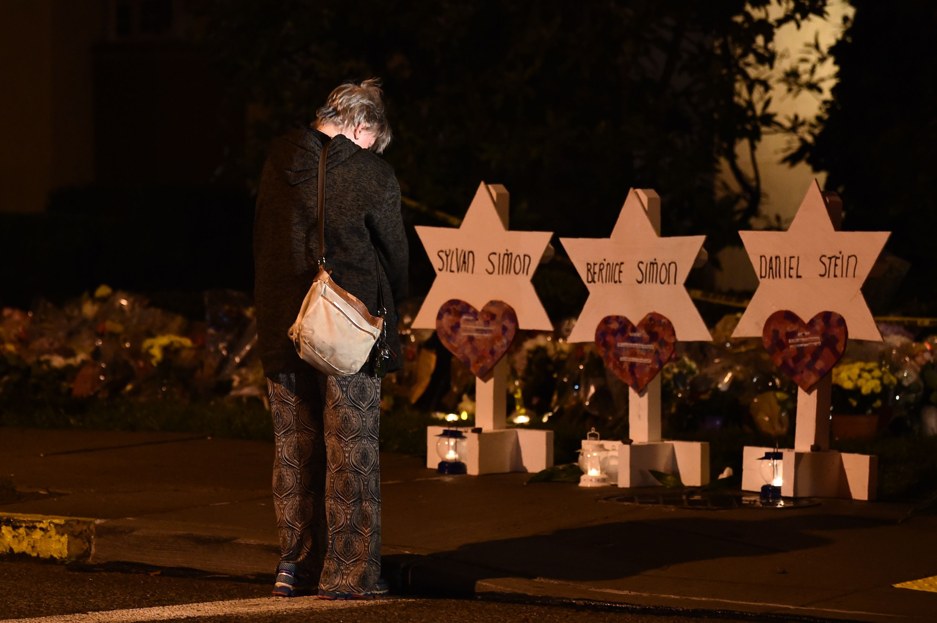 A woman bows her head in front of a memorial on October 28, 2018, at the Tree of Life synagogue after a shooting there left 11 people dead in the Squirrel Hill neighborhood of Pittsburgh on October 27. (BRENDAN SMIALOWSKI/AFP/Getty Images)