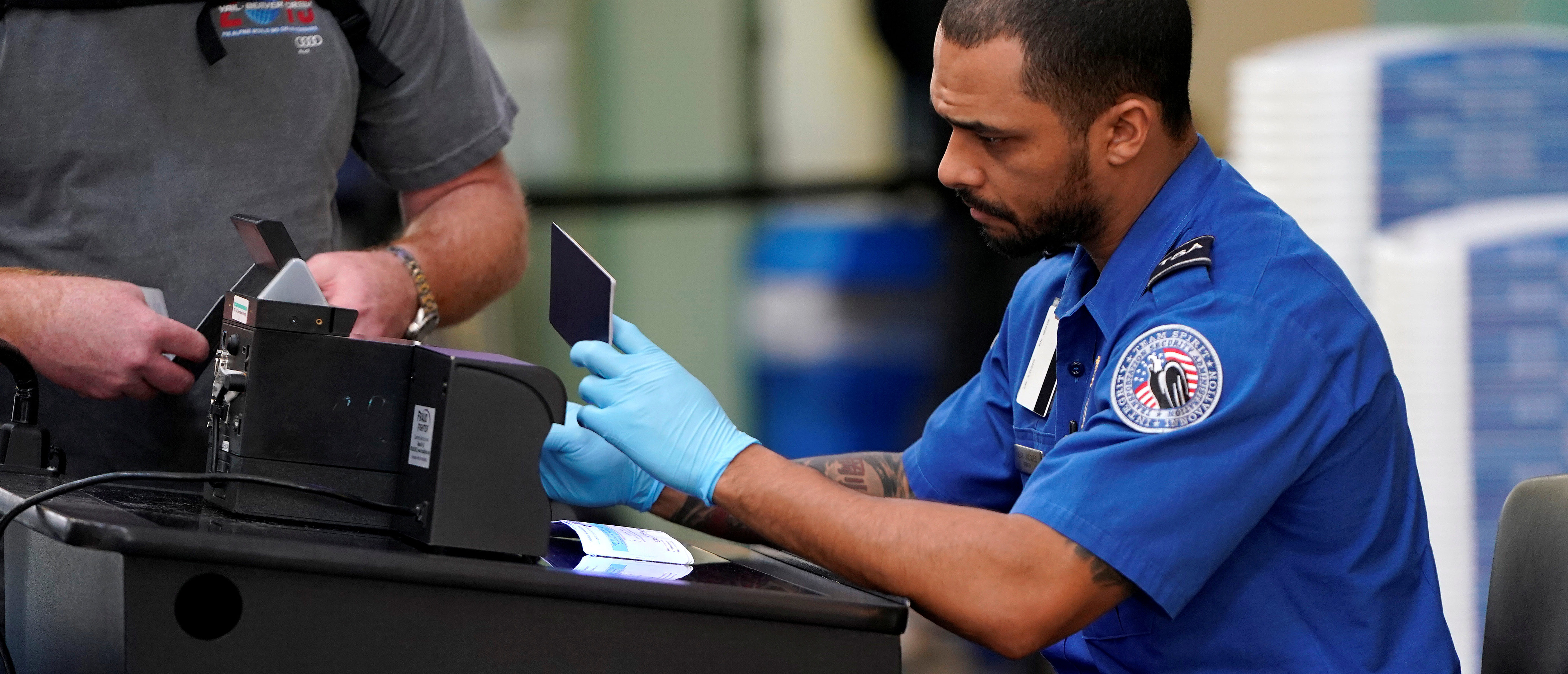 FILE PHOTO: An employee with the Transportation Security Administration (TSA) checks the documents of a traveler at Reagan National Airport in Washington, U.S., January 6, 2019. REUTERS/Joshua Roberts