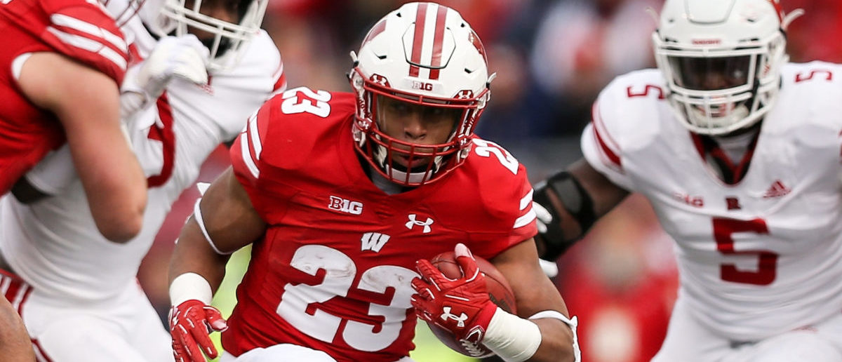 MADISON, WISCONSIN - NOVEMBER 03: Jonathan Taylor #23 of the Wisconsin Badgers runs with the ball while being chased by Isaiah Wharton #11 of the Rutgers Scarlet Knights in the first quarter at Camp Randall Stadium on November 03, 2018 in Madison, Wisconsin. (Photo by Dylan Buell/Getty Images)