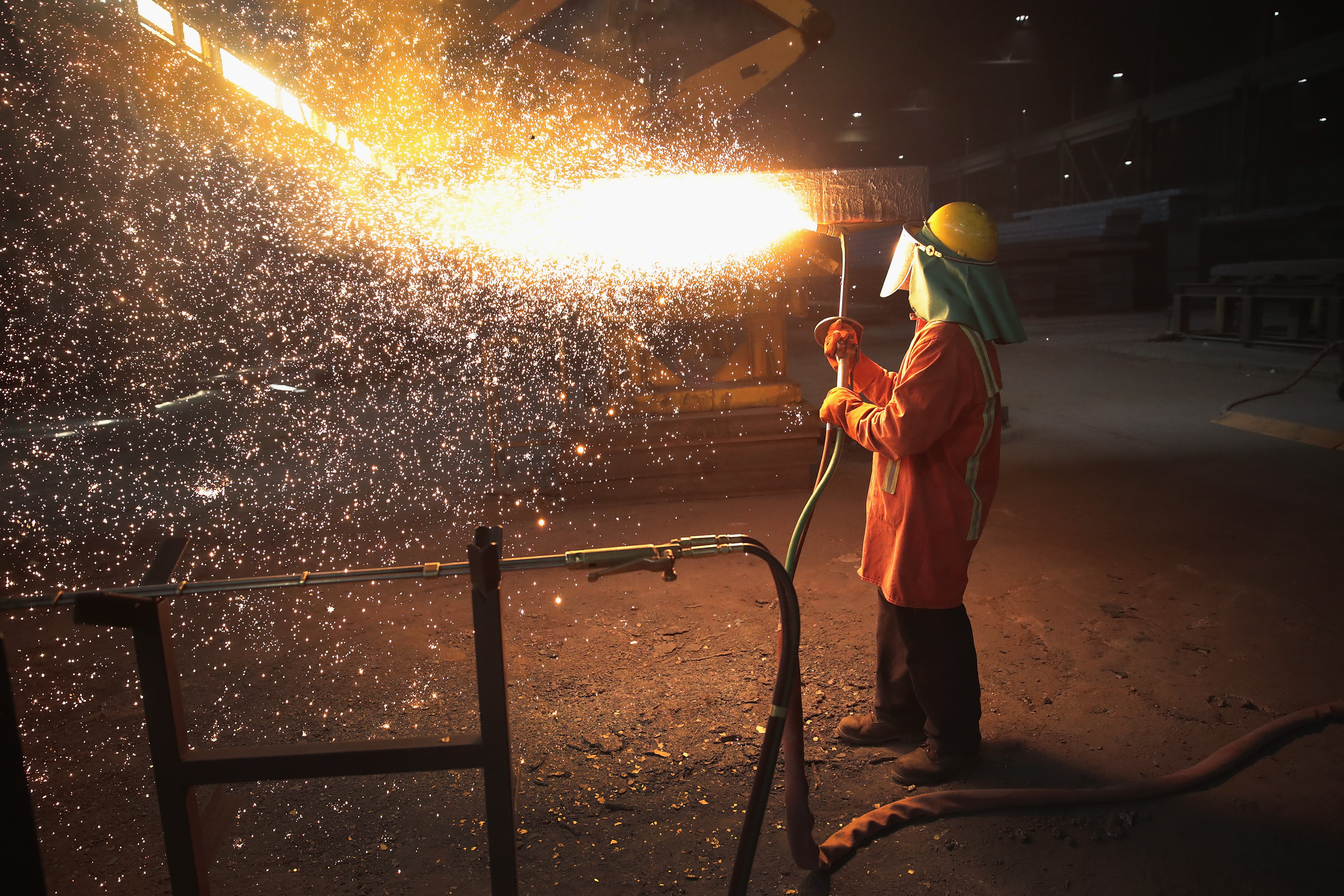 "PORTAGE, IN - MARCH 15: A worker trims a newly-cast steel slab at the NLMK Indiana steel mill on March 15, 2018 in Portage, Indiana. The mill, which is projected to produce up to 1 million tons of steel from recycled scrap in 2018, is considered a ""mini mill"" by U.S standards. NLMK Indiana is a subsidiary of NLMK, one of Russia's largest steel manufacturers, responsible for nearly a quarter of Russia's steel production and producing nearly a quarter of the worlds slab steel. Steel producers in the U.S. and worldwide are preparing for the impact of the recently-proposed tariffs by the Trump administration of 25 percent on imported steel. (Photo by Scott Olson/Getty Images)"