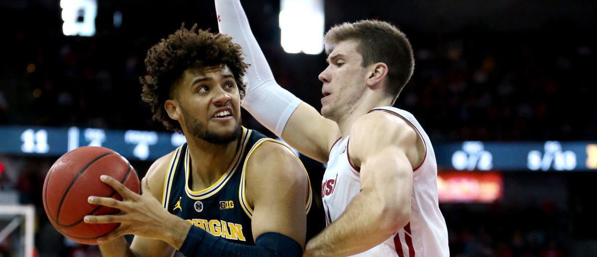 MADISON, WISCONSIN - JANUARY 19: Isaiah Livers #4 of the Michigan Wolverines handles the ball while being guarded by Ethan Happ #22 of the Wisconsin Badgers in the first half at the Kohl Center on January 19, 2019 in Madison, Wisconsin. (Photo by Dylan Buell/Getty Images)