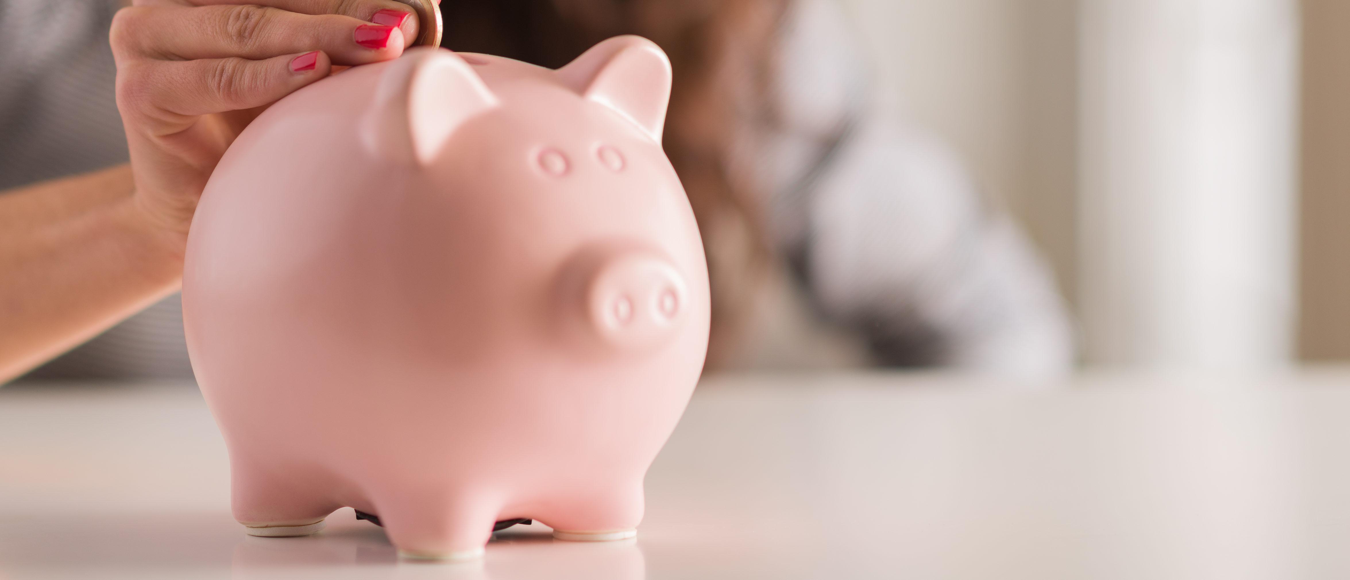 A woman puts a coin into a piggy bank (Shutterstock/Aaron Amat)