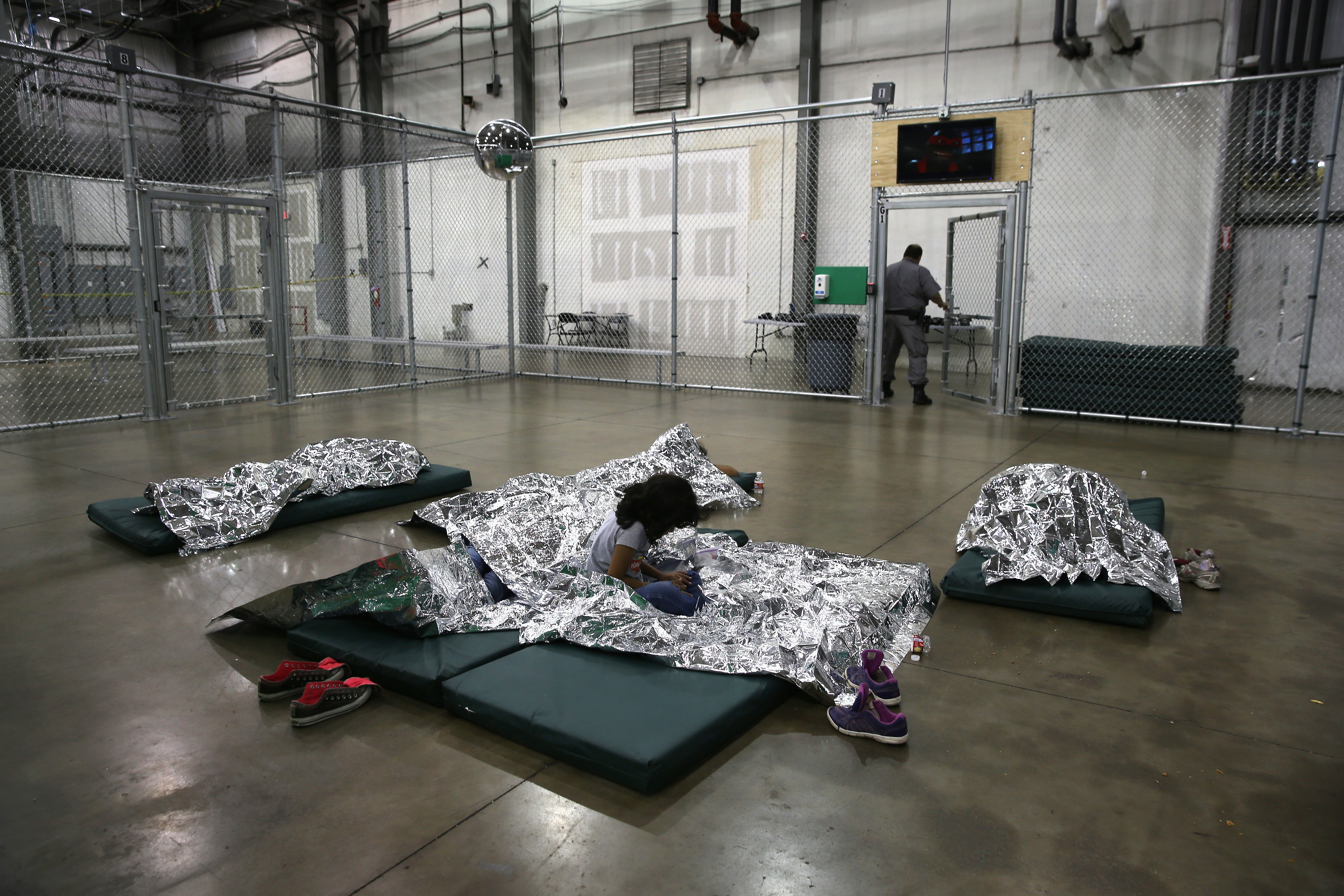 A girl from Central America rests on thermal blankets at a detention facility run by the U.S. Border Patrol on September 8, 2014 in McAllen, Texas. John Moore/Getty Images