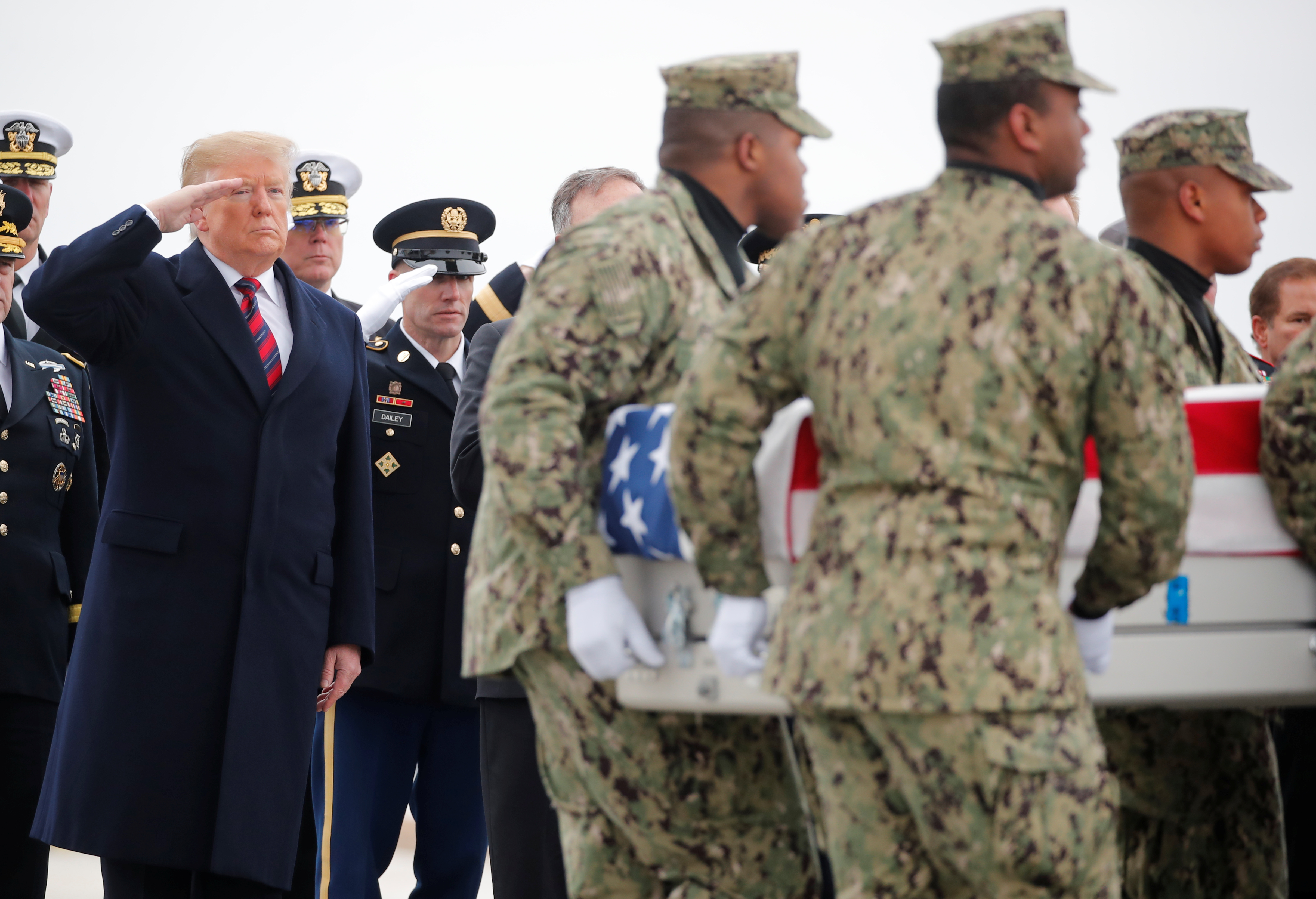 President Donald Trump salutes as a military honor guard carries the remains of Scott Wirtz, a civilian employee of the U.S. Defense Intelligence Agency killed along with three members of the U.S. military during a recent attack in Syria, past during a dignified transfer ceremony at Dover Air Force Base, in Dover, Delaware, U.S., January 19, 2019. REUTERS/Carlos Barria