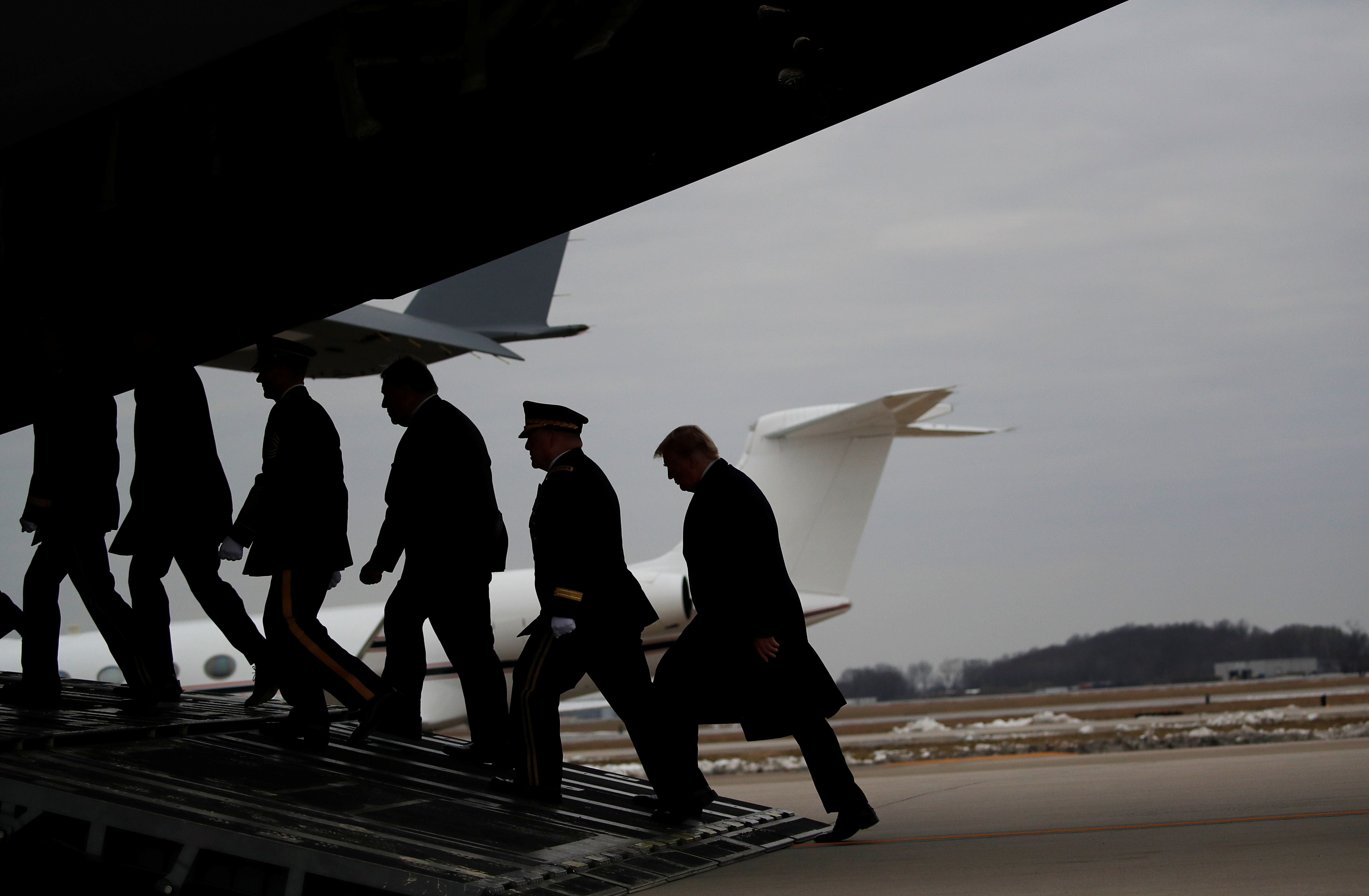 U.S. President Donald Trump follows U.S. military leaders, Secretary of State Mike Pompeo and a military honor guard into the back of an Air Force transport plane as they retrieve the remains of Scott Wirtz, a civilian employee of the U.S. Defense Intelligence Agency killed along with three members of the U.S. military during a recent attack in Syria, at the start of a dignified transfer ceremony at Dover Air Force Base, in Dover, Delaware, U.S., January 19, 2019. REUTERS/Carlos Barria