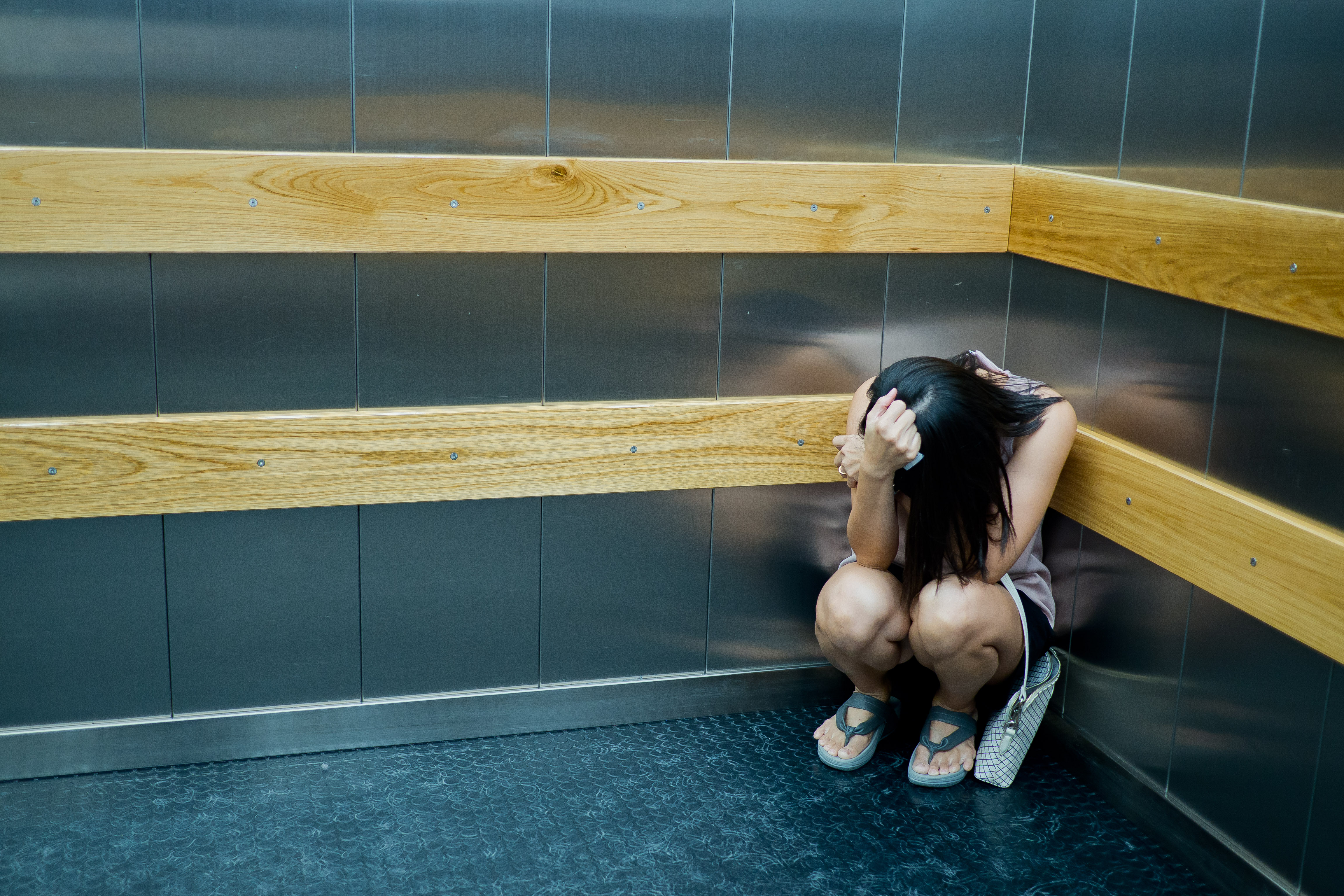Pictured is a woman stuck in an elevator. SHUTTERSTOCK/suriyachan