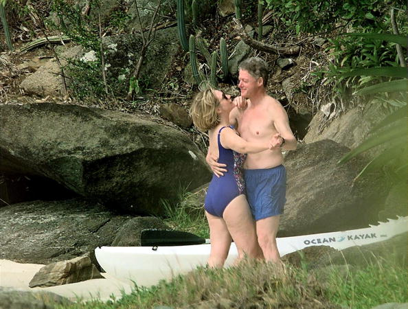 File photo dated 04 January 1998 shows US President Bill Clinton and First Lady Hillary Clinton dancing on the beach of Megan Bay, St. Thomas, US Virgin Islands shortly after taking a swim. (Photo by PAUL J. RICHARDS/AFP/Getty Images)