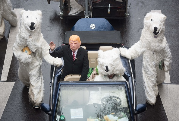 """A demonstrator dressed as US President Donald Trump waves from a car as he parades with other activists dressed as polar bears during a protest of the action group """"No Climate Change"""" on November 11, 2017 in Bonn, western Germany, where is taking place the COP23 United Nations Climate Change Conference. (BERND THISSEN/AFP/Getty Images)"""