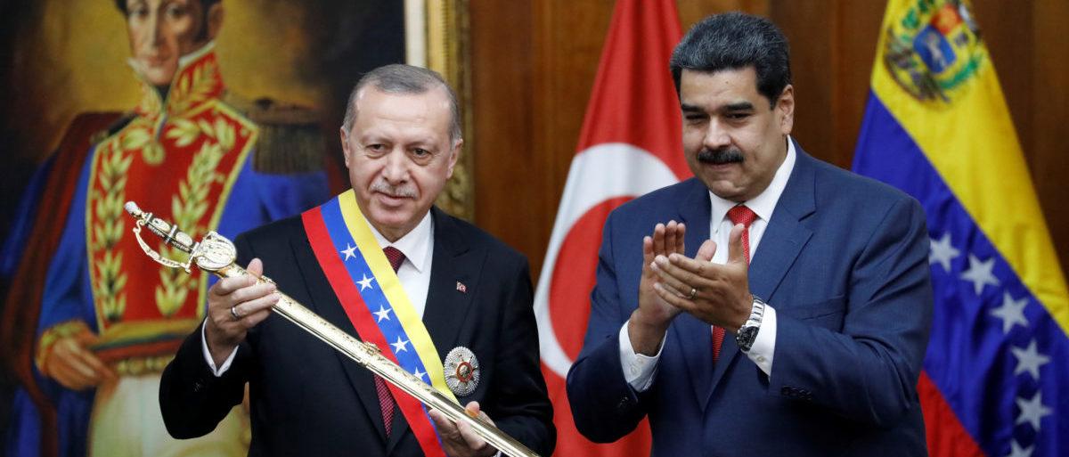 Turkish President Tayyip Erdogan holds a replica of the sword of national hero Simon Bolivar, next to Venezuela's President Nicolas Maduro, during an agreement-signing ceremony between Turkey and Venezuela at Miraflores Palace in Caracas, Venezuela December 3, 2018. REUTERS/Manaure Quintero