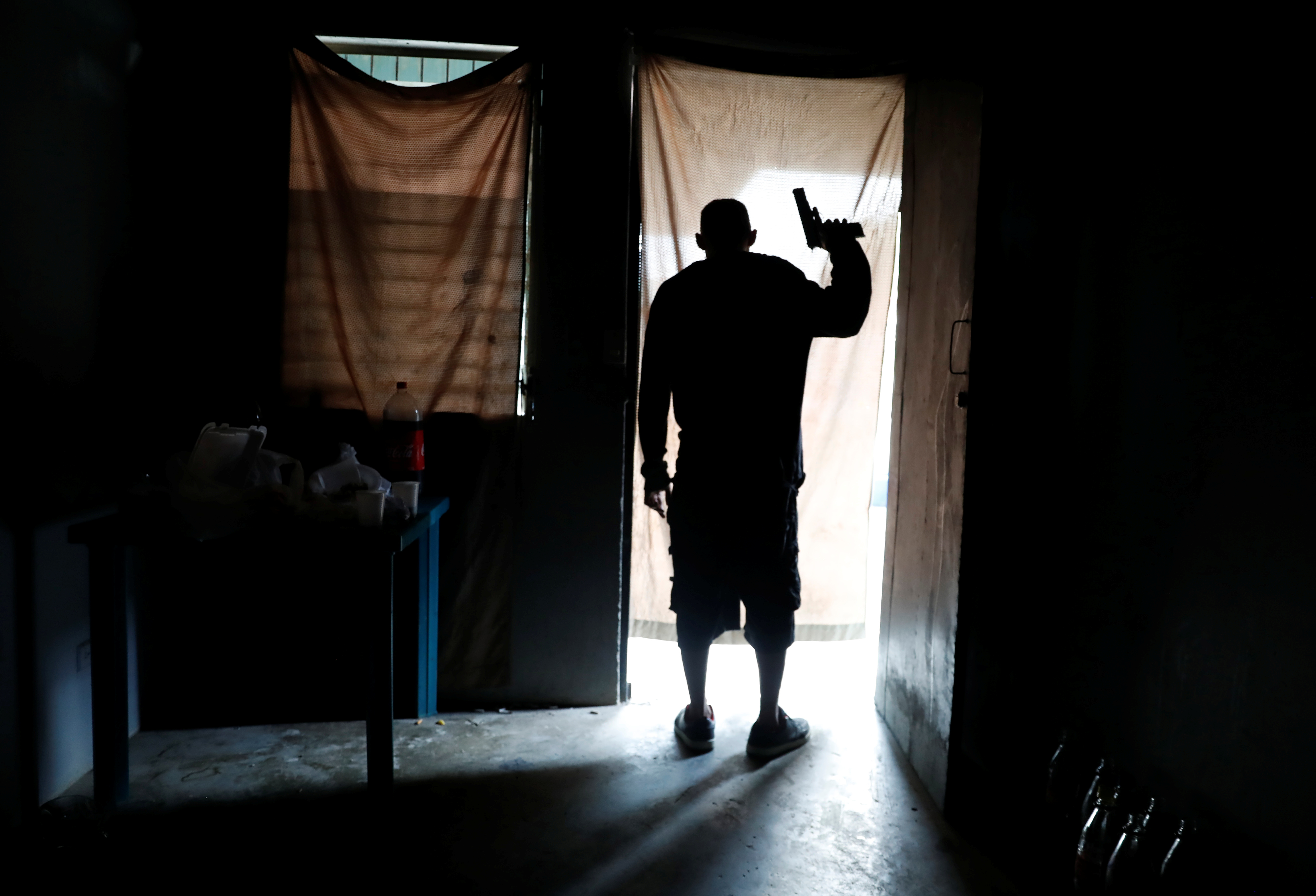 A member of MS-13 street gang looks out from a house as police patrol the street outside, in San Pedro Sula, Honduras September 29, 2018. The man was injured during a shoot-out between rival gangs MS-13 and Barrio 18 and died later of his injuries at a local hospital, according to a police report. REUTERS/Goran Tomasevic