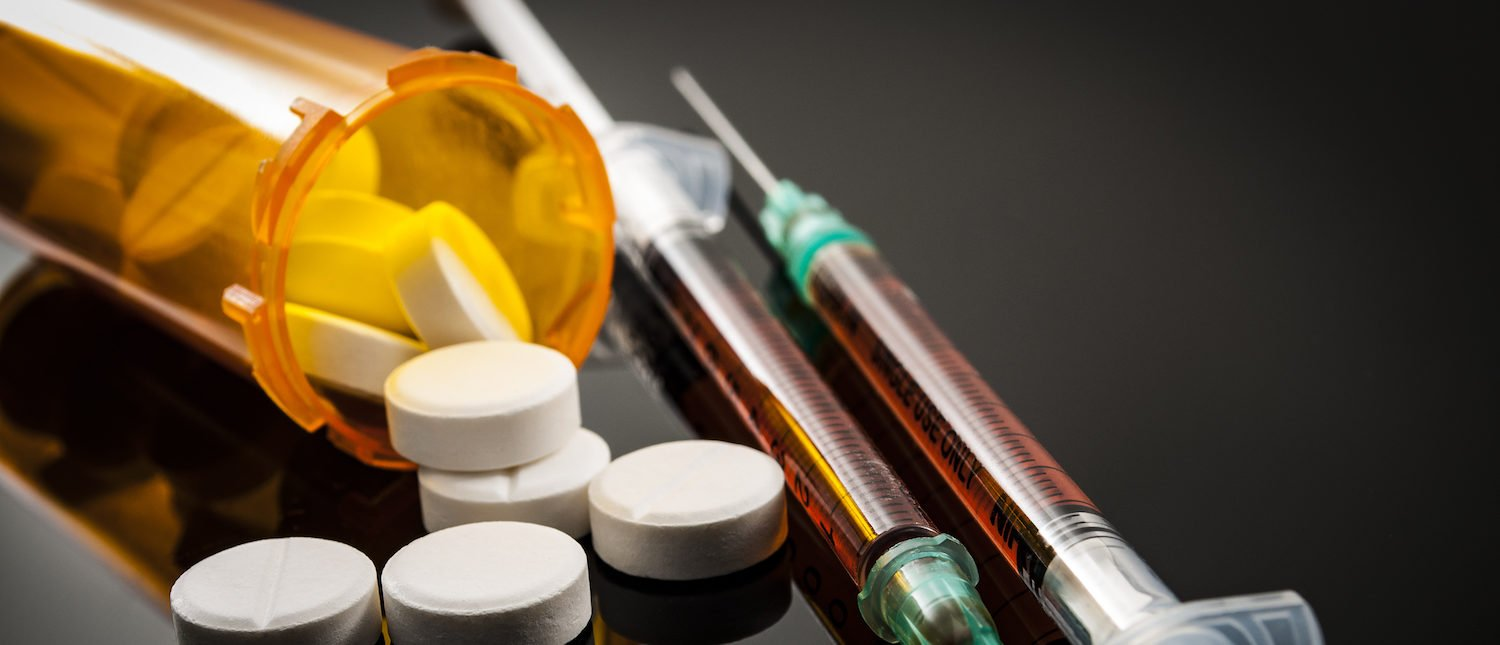 Opioid epidemic, drug abuse concept with closeup on two heroin syringes or other narcotics surrounded by scattered prescription opioids. Oxycodone is the generic name for a range of opioid painkillers. Shutterstock/Victor Moussa