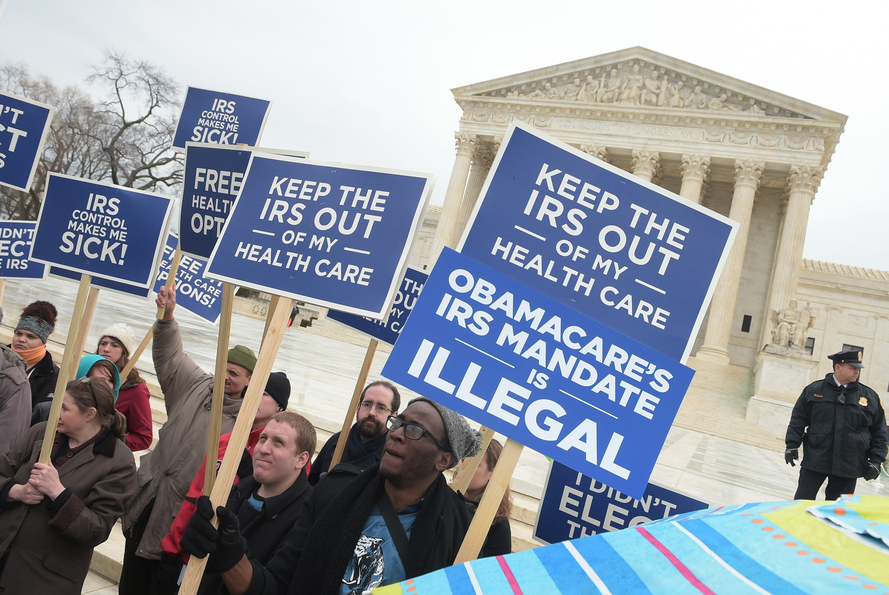 """Protestors hold placards challenging """"Obamacare"""" outside of the Supreme Court on March 4, 2015. (Mandel Ngan/AFP/Getty Images)"""