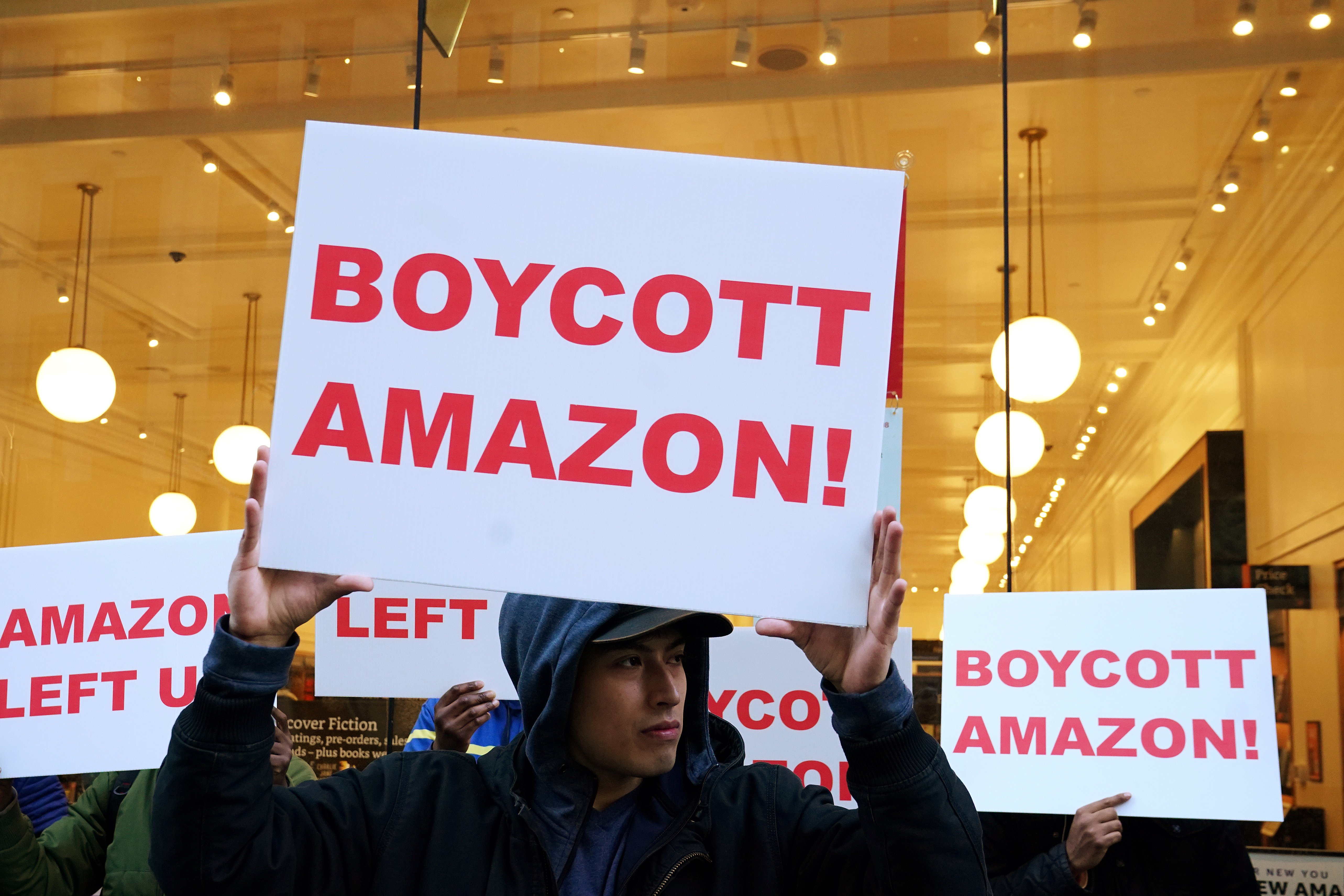 People stand in front of an Amazon store and protest Amazon's change in mind to not open an office in Queens, in the Manhattan borough of New York City, New York, U.S., February 15, 2019. REUTERS/Carlo Allegri