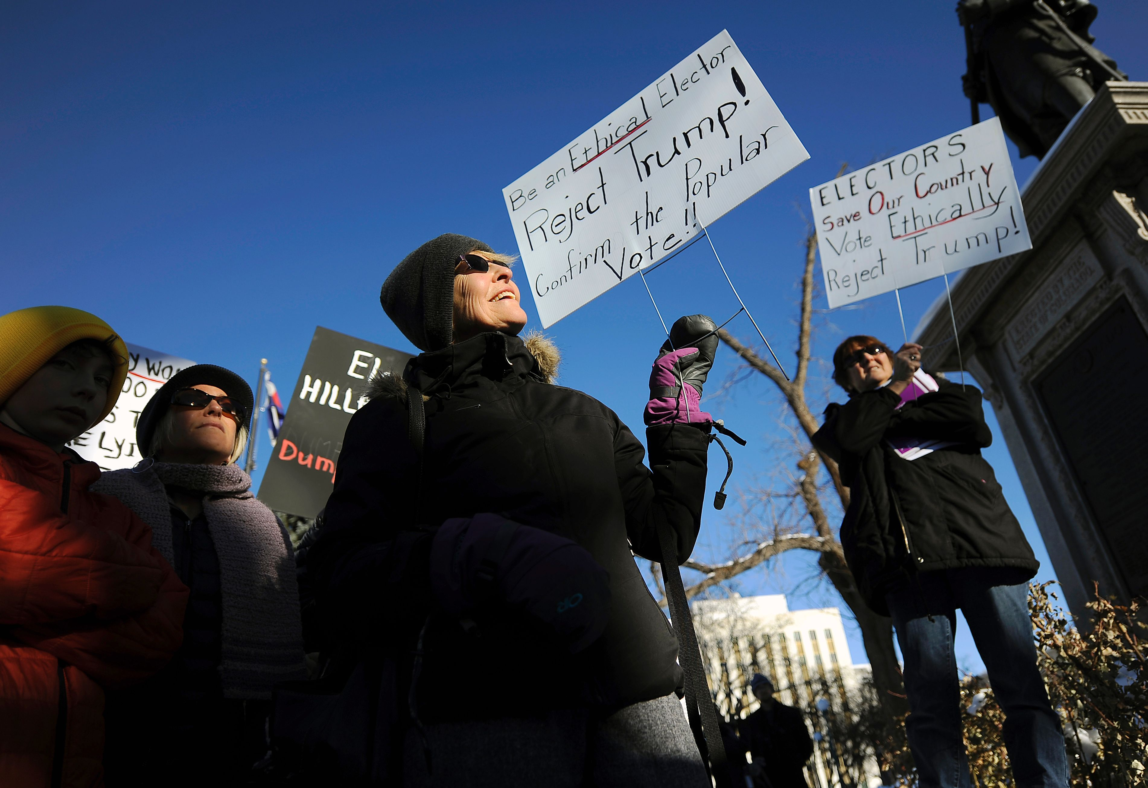 People protest outside the Colorado Capitol building in Denver, Colorado on December 19, 2016 to demonstrate against US President-elect Donald Trump on the day the Electoral College votes to certify the election. Members of America's Electoral College convened across the country Monday to formally anoint Donald Trump as president, with opponents clinging to slim hopes of a revolt that could deny him power. / AFP / Chris Schneider (Photo credit should read CHRIS SCHNEIDER/AFP/Getty Images)