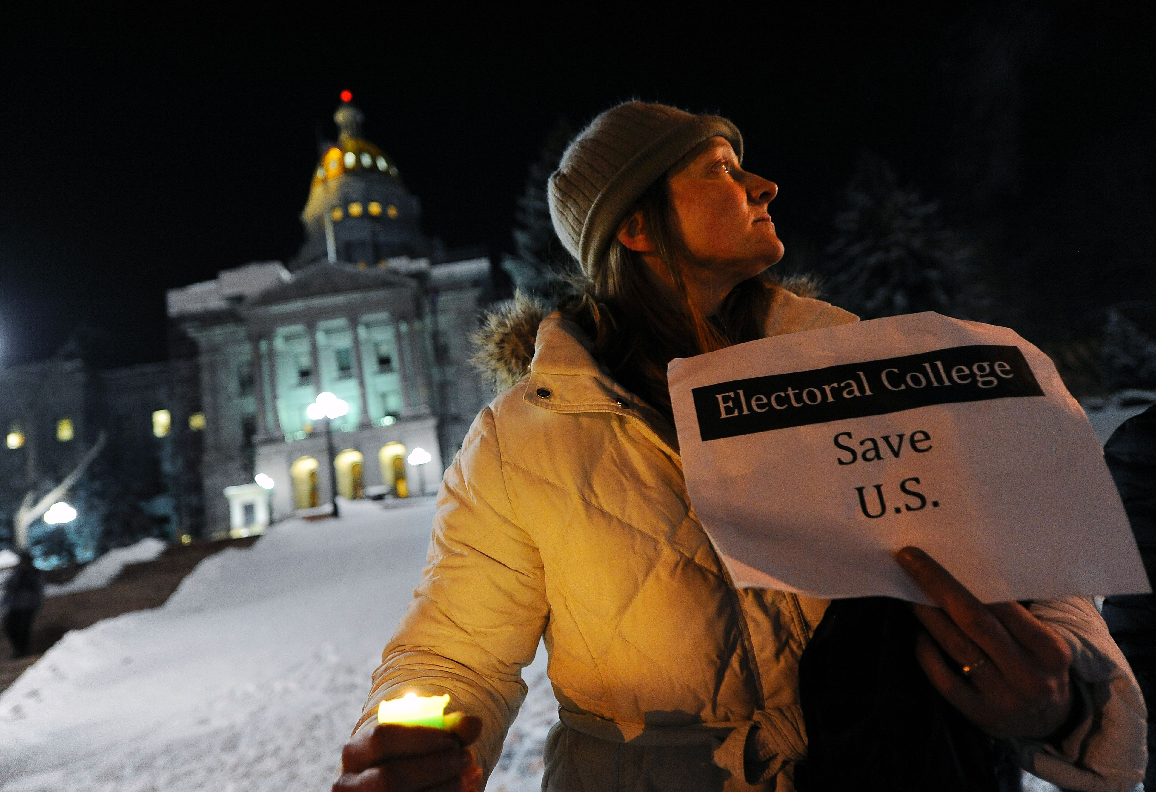 "Ruth Fulton, 44, demonstrates during a candlelight vigil against US President-elect Donald Trump outside the Colorado Capitol building on the eve of the Electoral College vote, in Denver, Colorado on December 18, 2016. ""The Electoral College is supposed to be a safeguard against exactly this sort of person,"" said Fulton. CHRIS SCHNEIDER/AFP/Getty Images"