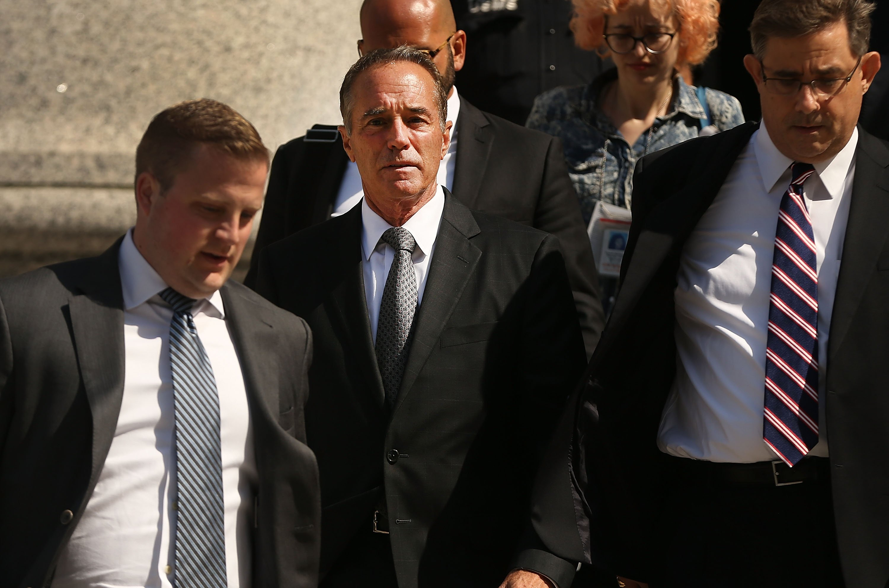 Rep. Chris Collins (2nd L) walks out of a New York court house after being charged with insider trading on August 8, 2018 in New York City. (Photo by Spencer Platt/Getty Images)