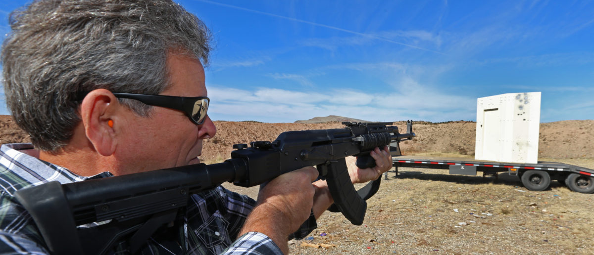 """CEO of """"Shelter in Place"""" Jim Haslem, fires an AK-47 assault rifle into one of his bullet resistant shelters on October 25, 2018 in Cedar City, Utah. (Photo by George Frey/Getty Images)"""