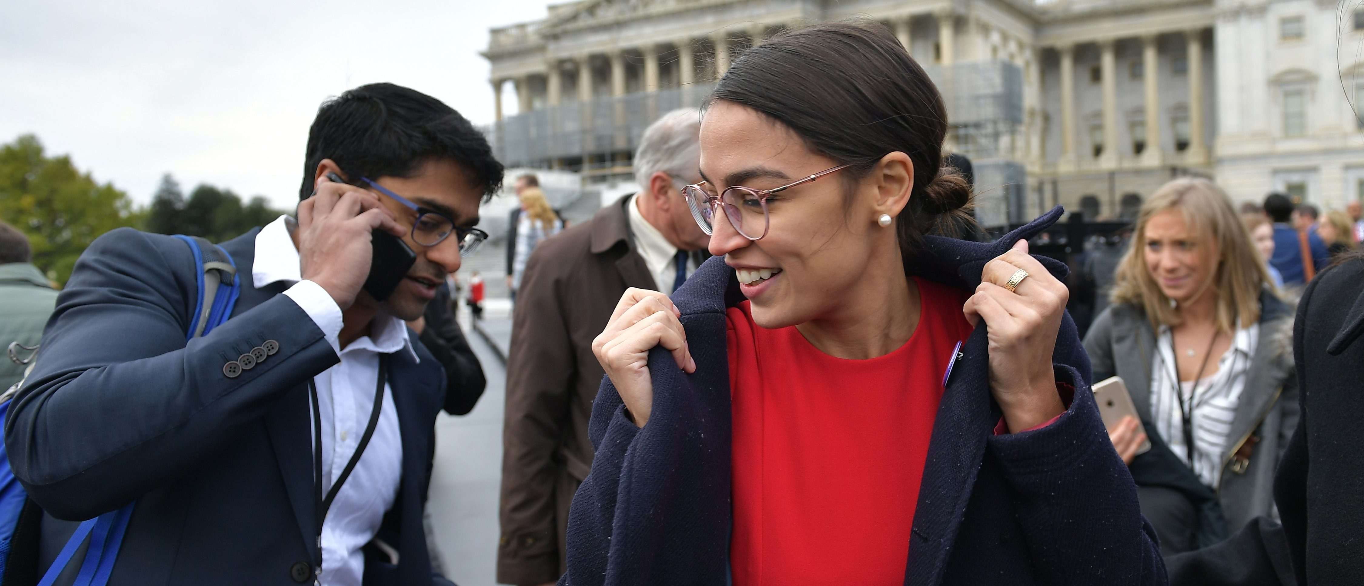 Democratic congresswoman-elect Alexandria Ocasio-Cortez puts on her coat after posing for the 116th Congress members-elect group photo on the East Front Plaza of the US Capitol in Washington, DC on November 14, 2018. (Photo credit: MANDEL NGAN/AFP/Getty Images)