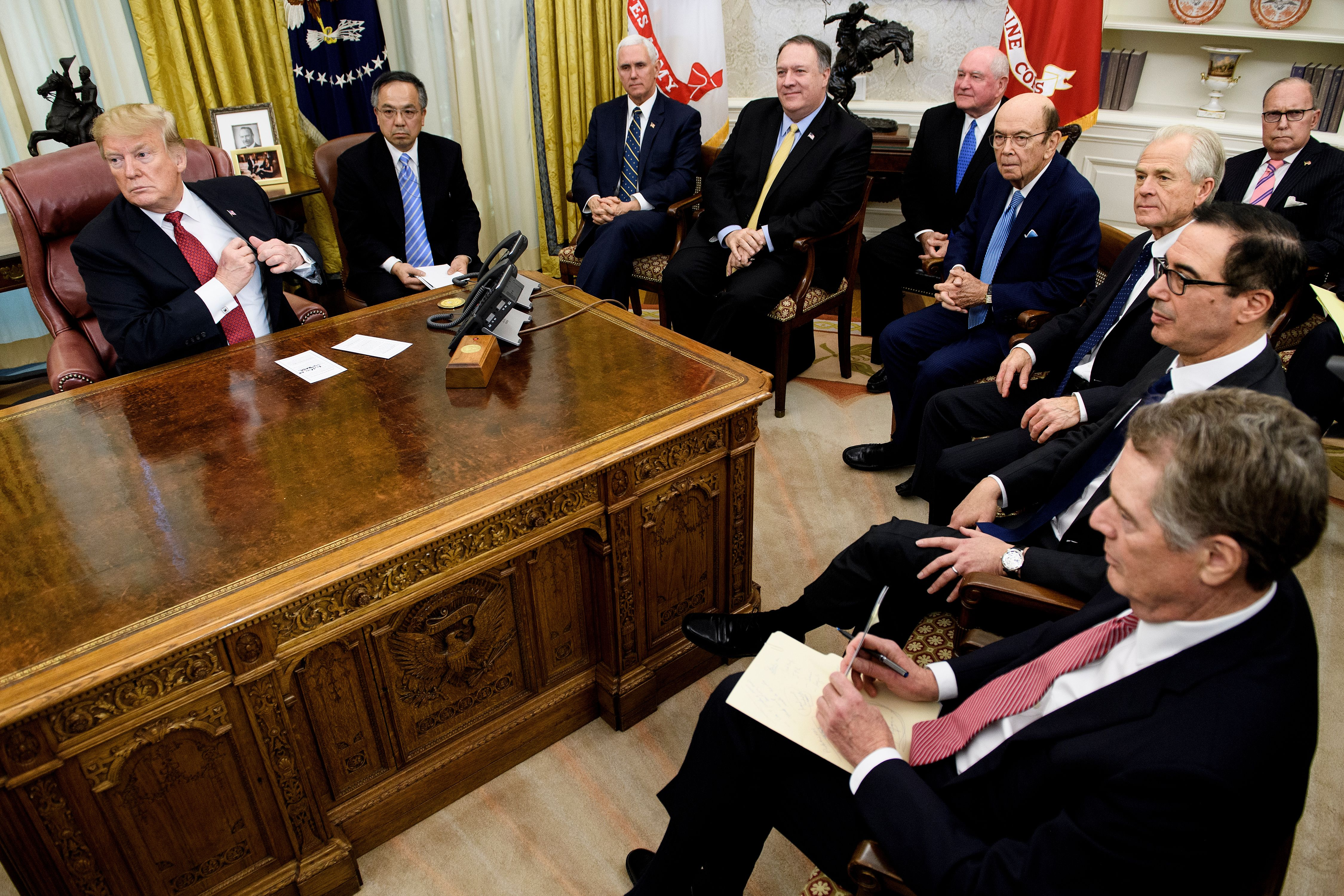 US President Donald Trump (L) waits with US Vice President Mike Pence (3L), US Secretary of State Mike Pompeo (4L), US Secretary of Agriculture Sonny Perdue (5L), US Secretary of Commerce Wilbur Ross (5R), Peter Navarro (4R), US Trade Representative Robert Lighthizer (3R), US Secretary of the Treasury Steven Mnuchin (2R), National Economic Council Director Larry Kudlow (R) and others for a meeting with China's Vice Premier Liu He and other Chinese officials in the Oval Office of the White House January 31, 2019 in Washington, DC. (Photo by BRENDAN SMIALOWSKI/AFP/Getty Images)