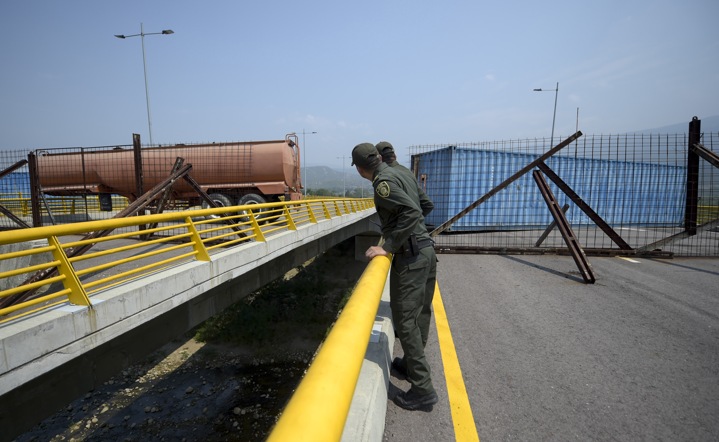 Colombian policemen look at the Tienditas Bridge, which links Tachira, Venezuela, and Cucuta, Colombia, after it was blocked with containers by Velezuelan forces, on February 6, 2019. (RAUL ARBOLEDA/AFP/Getty Images)