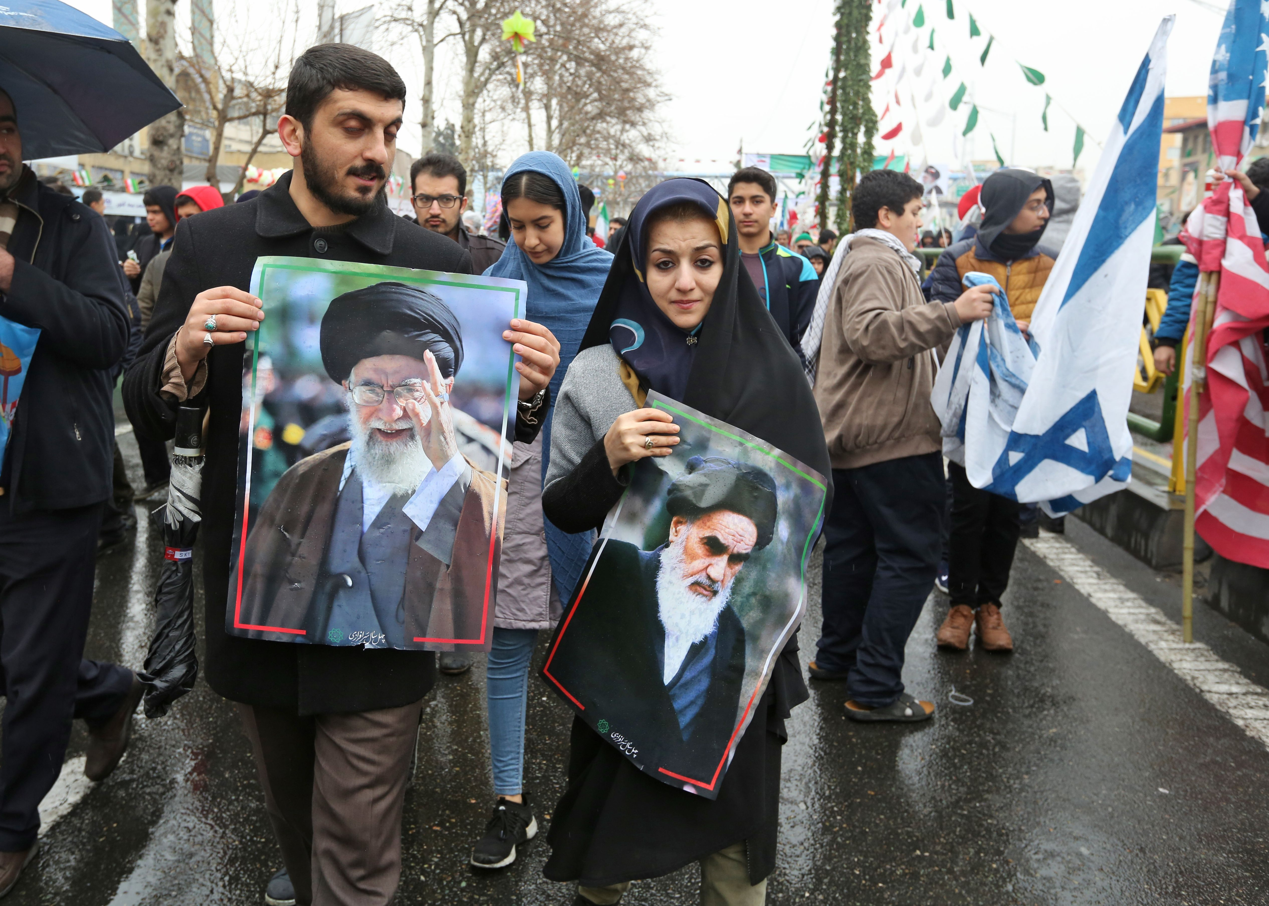 An Iranian man marches with a portrait of the country's Supreme Leader Ali Khamenei (L) alongside a woman holding up another of Islamic Revolution founder Ayatollah Ruhollah Khomeini (R) during a ceremony celebrating the 40th anniversary of Islamic Revolution in the capital Tehran on February 11, 2019. (ATTA KENARE/AFP/Getty Images)