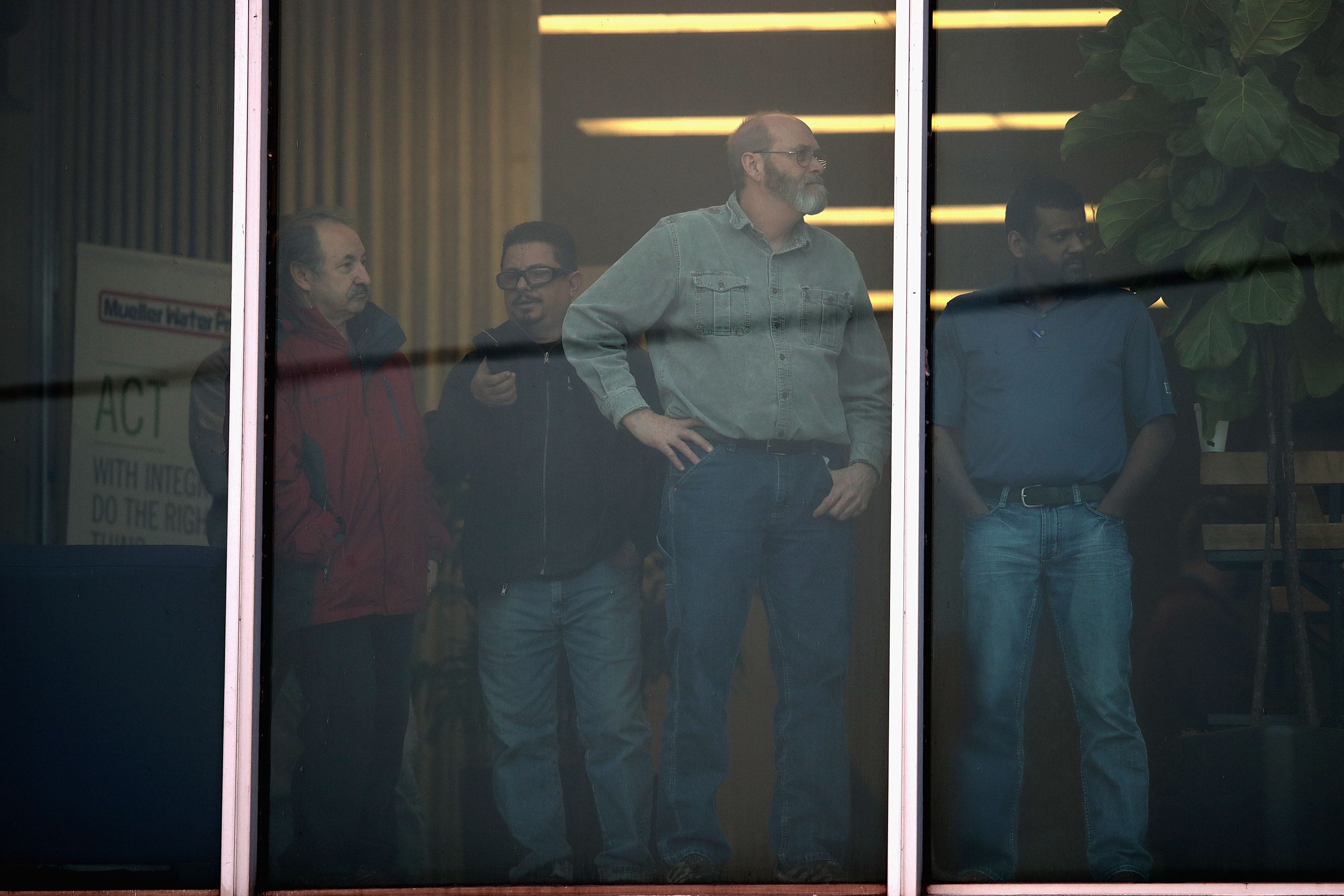 Workers look out an office window following a shooting at the Henry Pratt Company on February 15, 2019 in Aurora, Illinois. (Photo by Scott Olson/Getty Images)