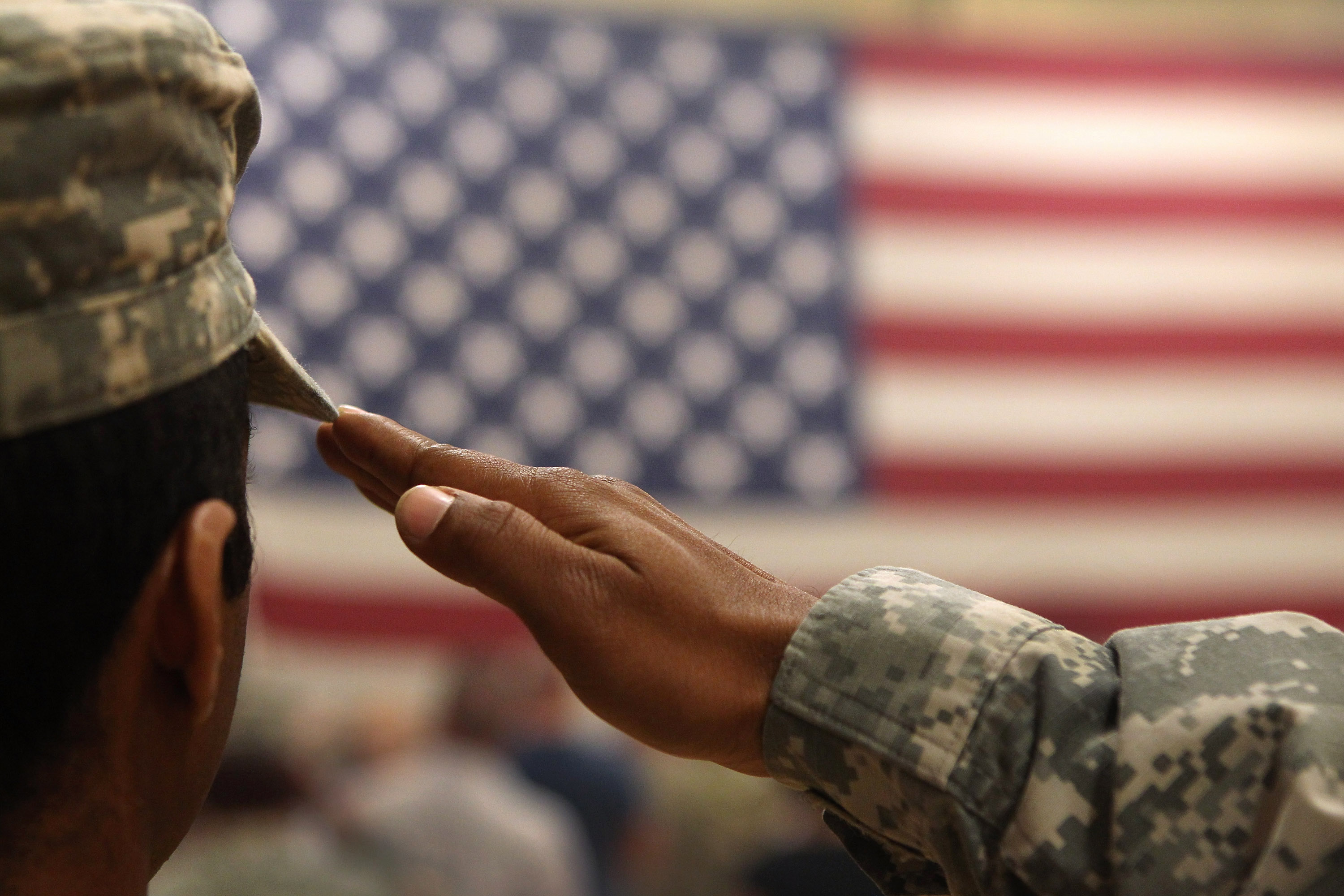 A soldier salutes the flag during a welcome home ceremony for troops arriving from Afghanistan on June 15, 2011 to Fort Carson, Colorado. (Photo by John Moore/Getty Images)