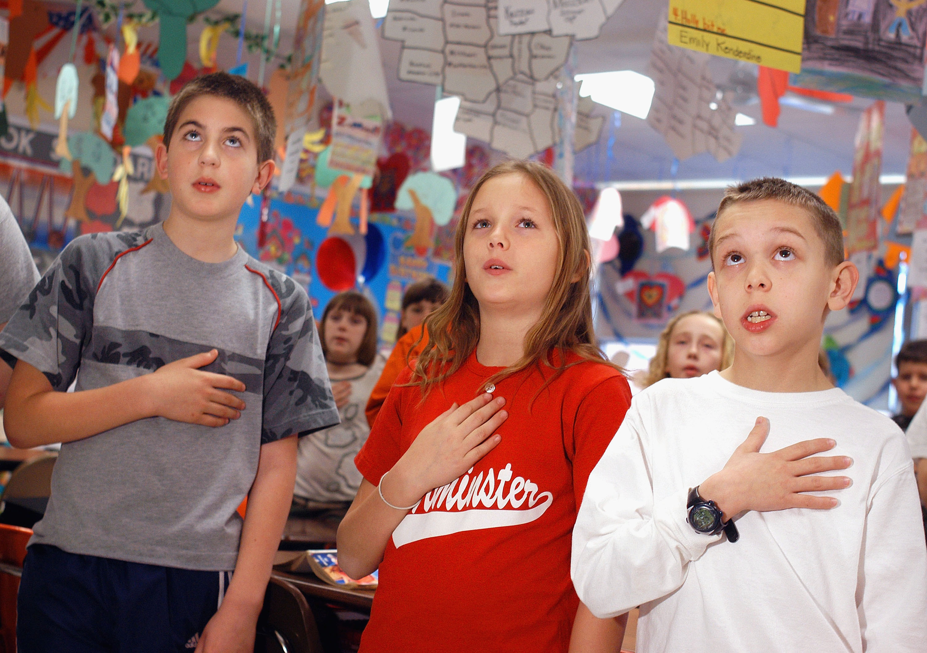 (L-R) Kevin Flynn, Brooke Zumwalt and Joseph Miller, fourth grade students at Longstreth Elementary School pledge allegiance to the flag March 24, 2004 in Warminster, Pennsylvania. (Photo by William Thomas Cain/Getty Images)