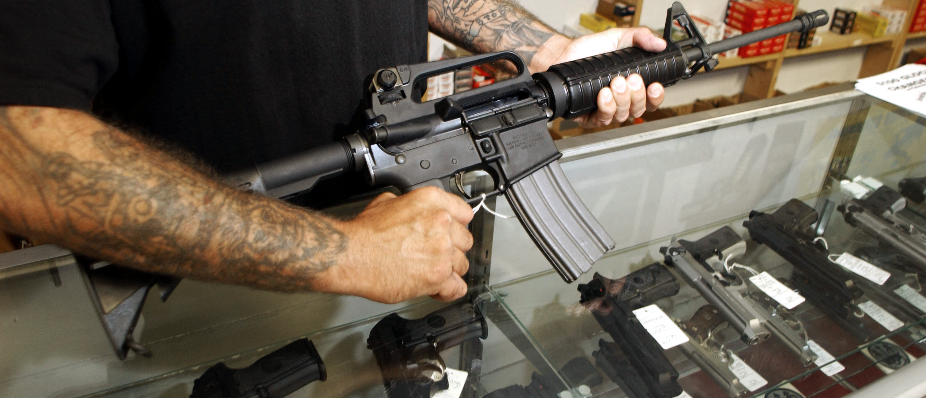 An employee of Dave's Guns holds a Colt AR-15, now legal with a bayonet mount, flash suppressor, collapsible stock and a high capacity magazine that holds more than 30 rounds, September 13, 2004 in Denver, Colorado.(Photo by Thomas Cooper/Getty Images)