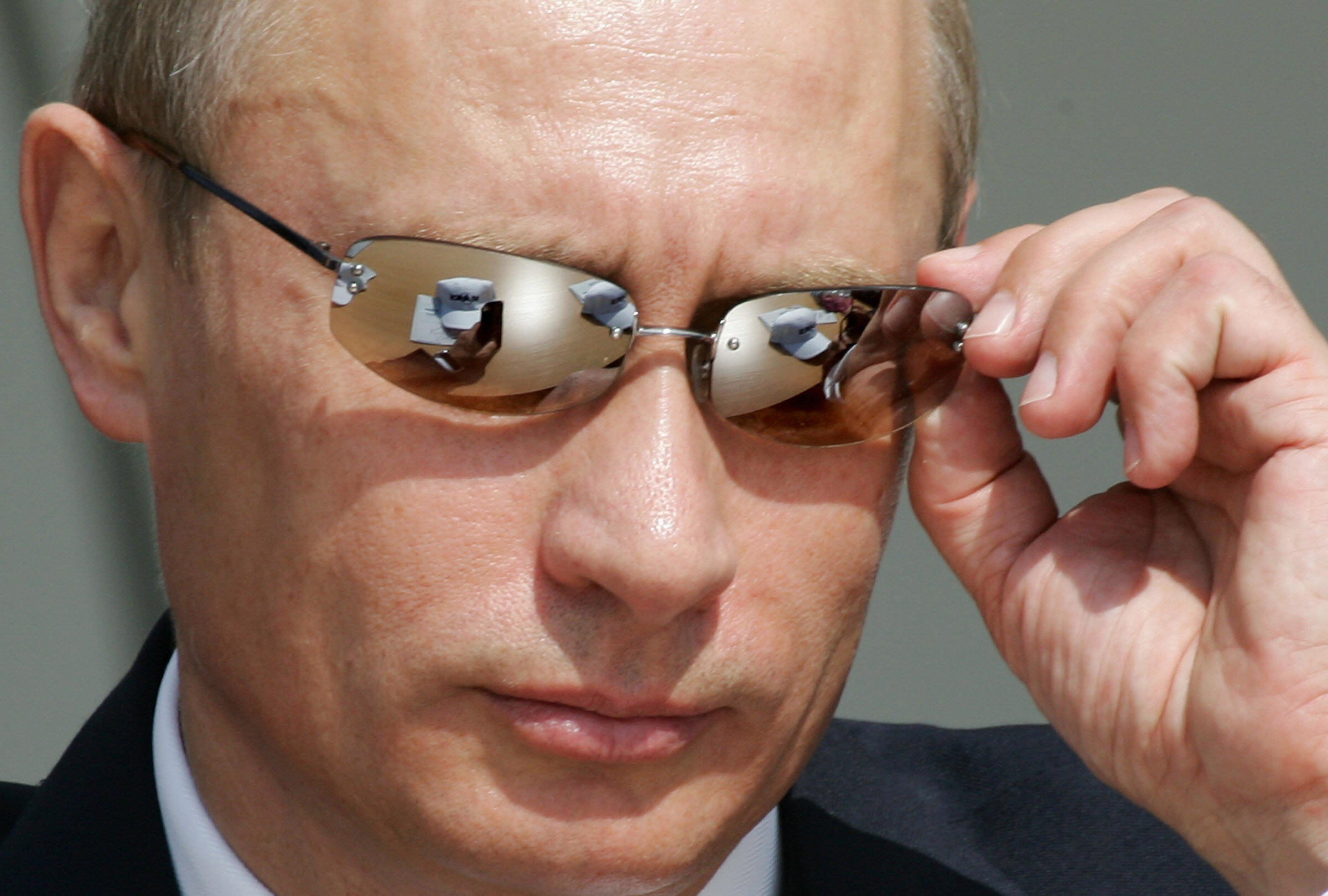 Russian President Vladimir Putin adjusts his sunglasses during the MAKS-2005 International air and space show in Zhukovsky, some 50 kms from Moscow, 16 August 2005. AFP PHOTO / MLADEN ANTONOV/ Getty Images